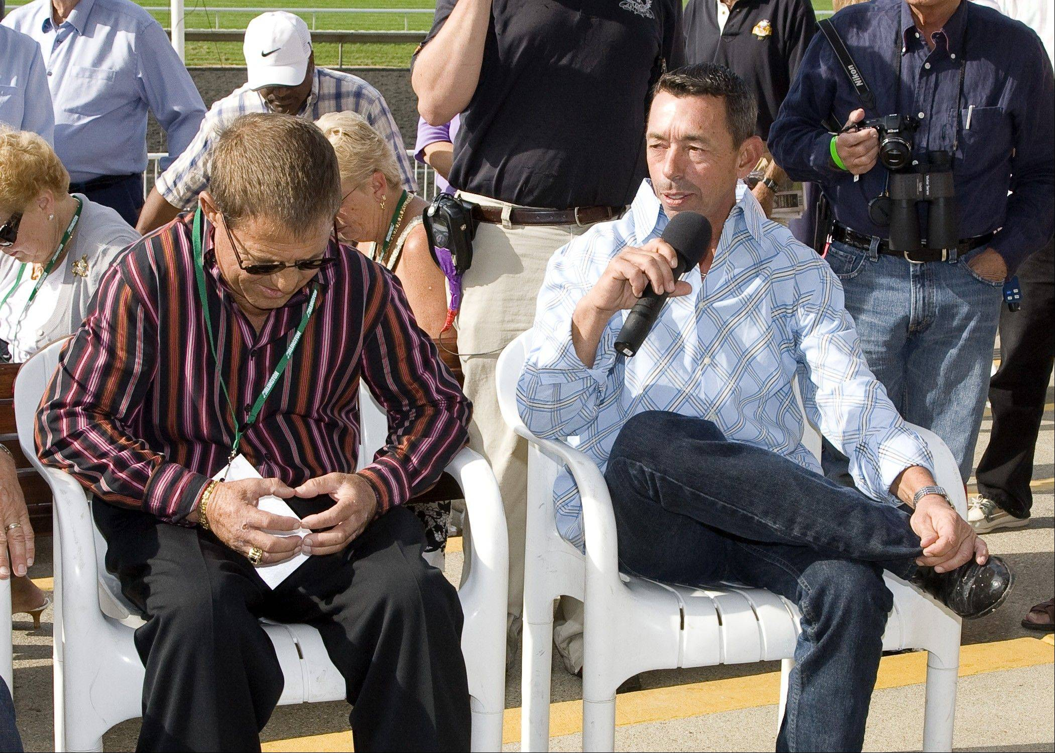 Randy Romero, left, listens as veteran jockey Mark Guidry talks Friday before making his return to racing in the jockeys vs. legends race at Arlington Park.