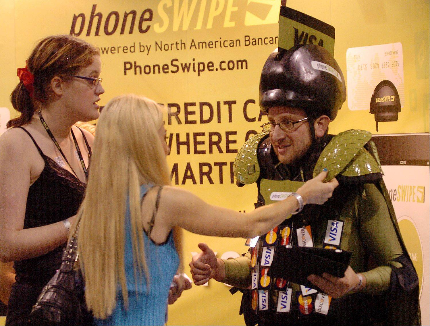 Kat Berry, left, and Anna Nowicka help Phone Swipe Man with his costume at the Wizard World Chicago Comic Con.