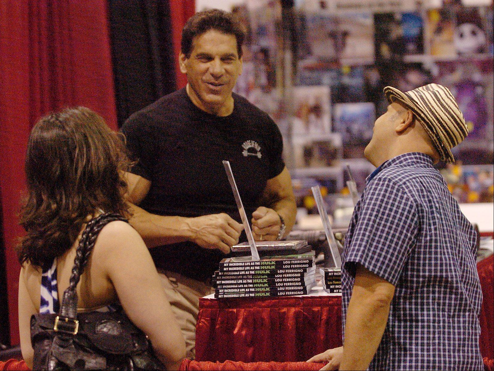 Lou Ferrigno visits with Paris Themmen, right, who played Mike TeeVee in Willie Wonka, and Nikki Grillos, as he prepares to sign his book at the Wizard World Chicago Comic Con.