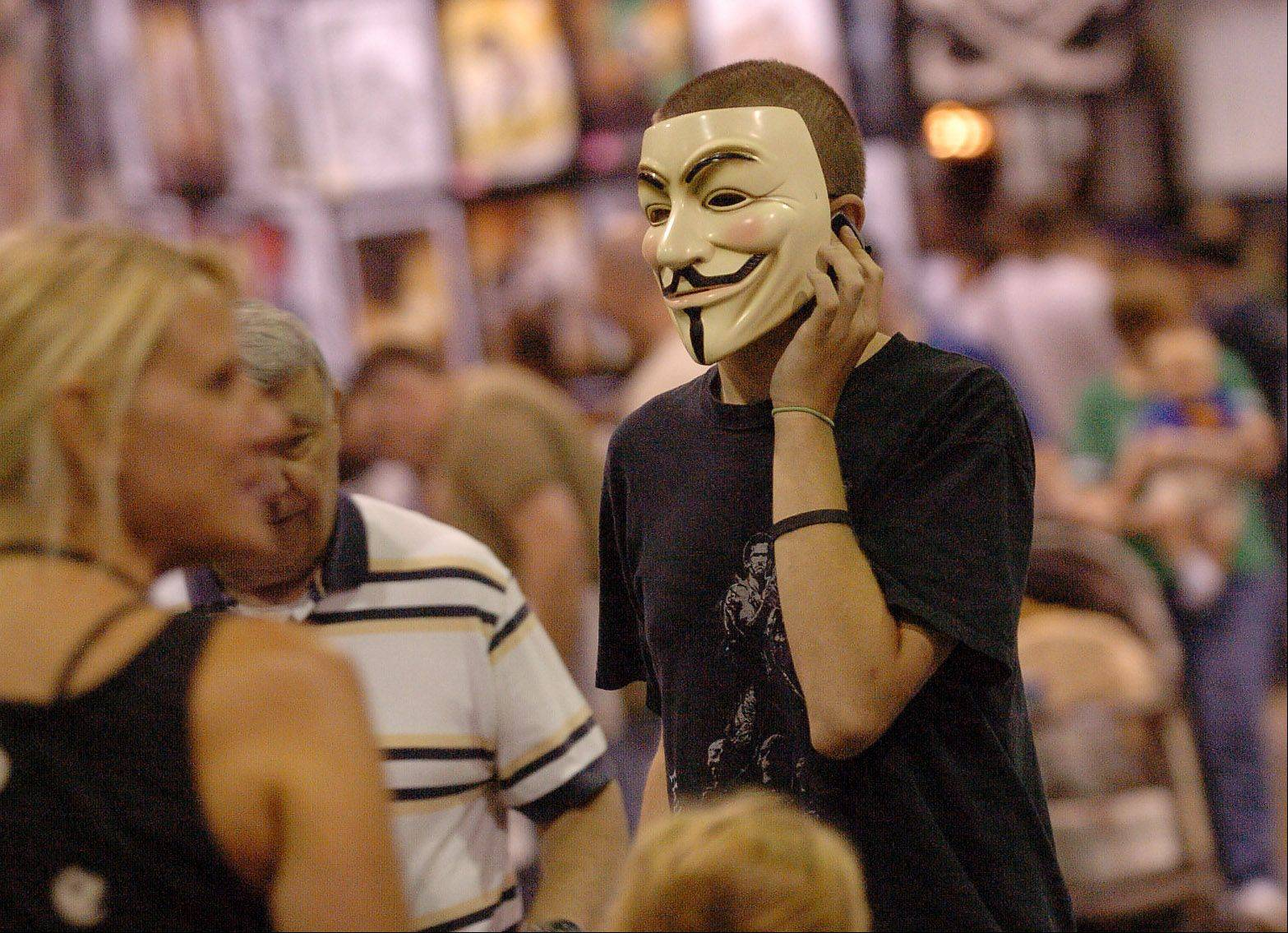 Alek Miser of Wheaton, on his cellphone while wearing a Guy Fawkes mask from the comic book V for Vendetta at the Wizard World Chicago Comic Con.