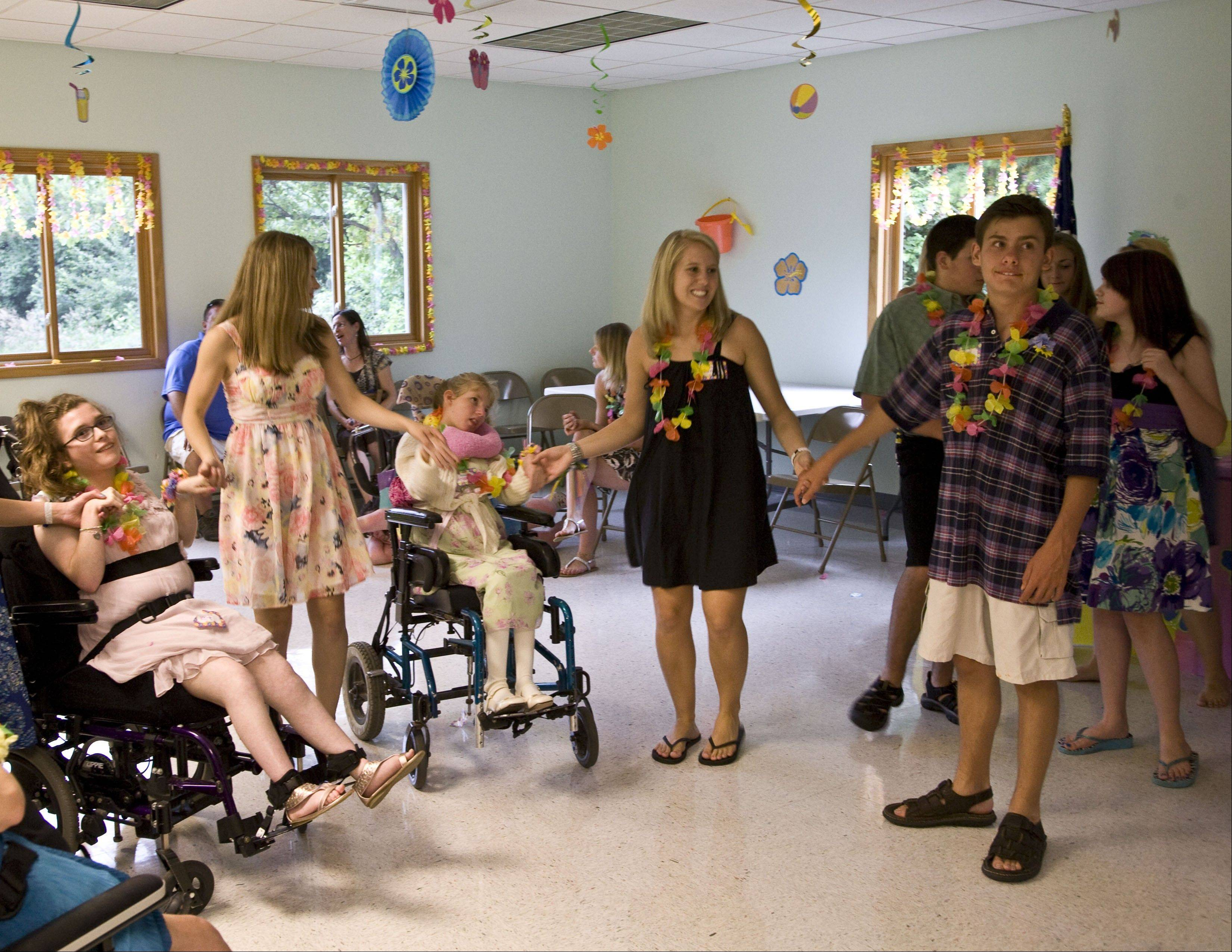Volunteers Megan Richmond, standing left, Chassidy Mangers and Sean Stanton mix with guests at a dance Mangers arranged earlier this month at the Blackberry Township Town Hall. The dance was for children with special needs.