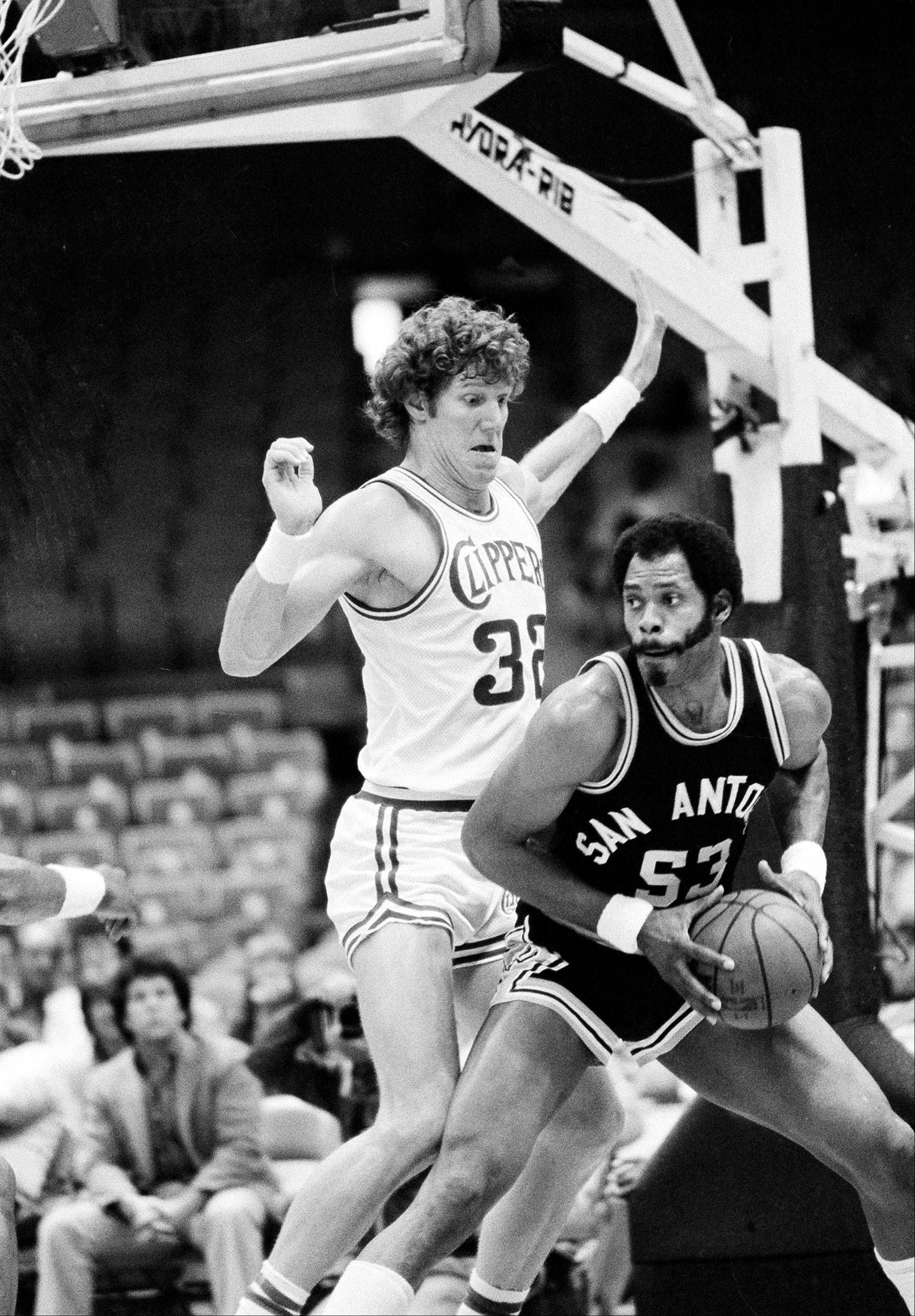 Artis Gilmore of the San Antonio Spurs gets ready to drive to the basket against Bill Walton of the San Diego Clippers in San Diego, Ca., on March 5, 1983.