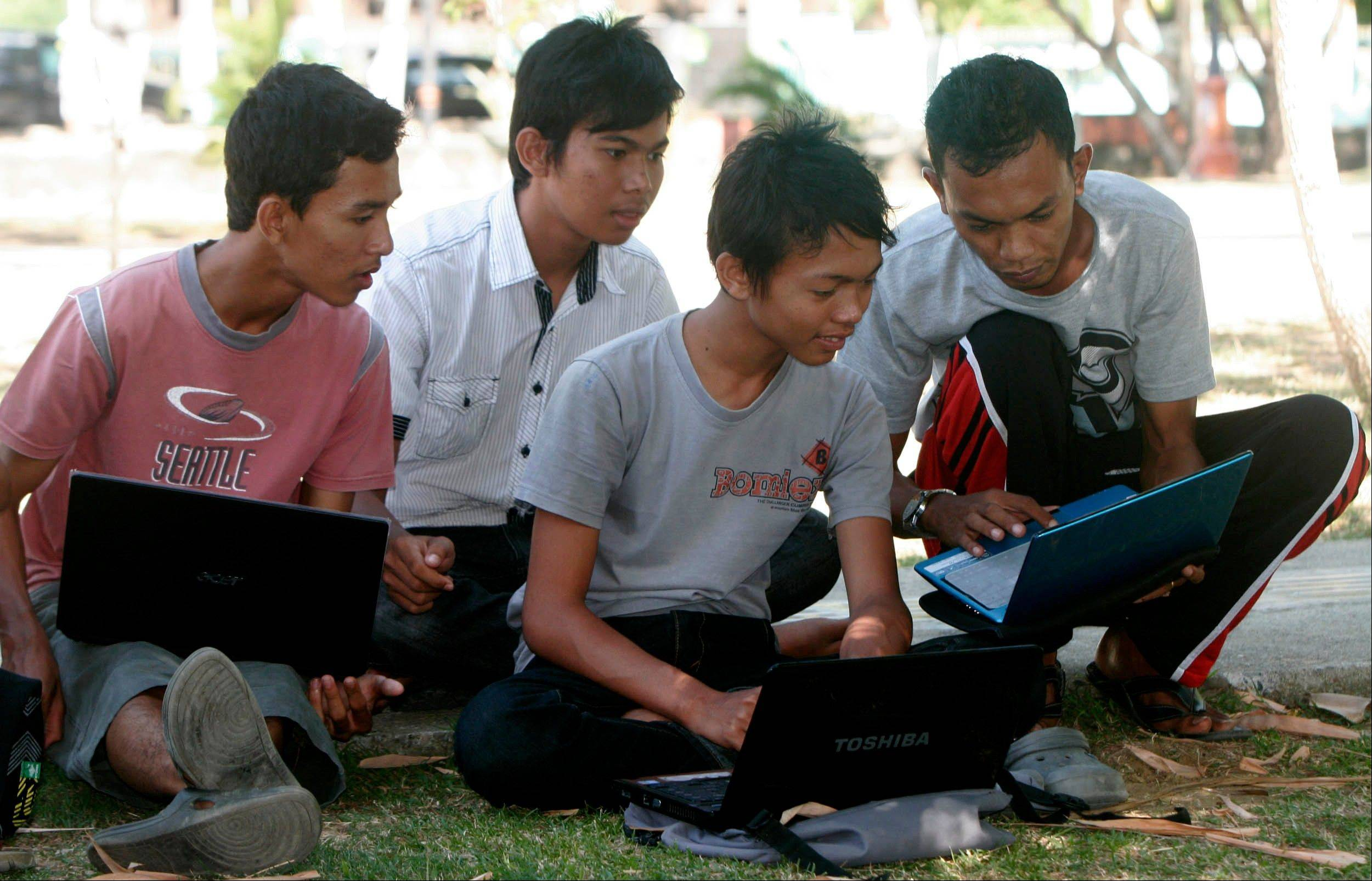 Young people browse Internet using free Wi-Fi access at a park in Indonesia.