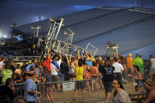 Fans waiting to see Sugarland attempt to hold up the stage after high winds blew the stage over at the Indiana State Fair Grandstands, Saturday, Aug. 13, 2011, in Indianapolis.