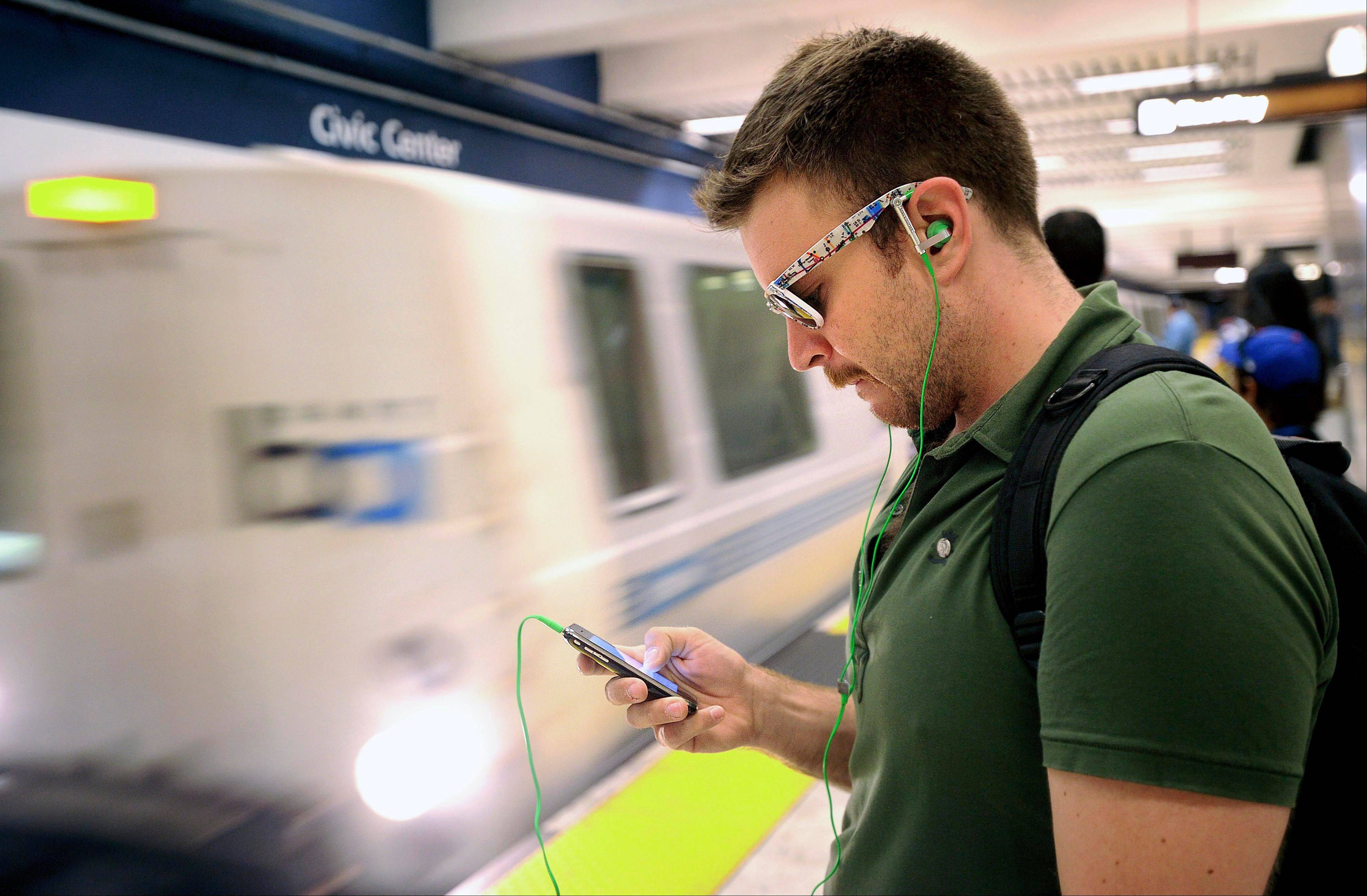 Nick Sabatasso checks his cell phone Saturday while waiting for a BART train at San Francisco�s Civic Center station.