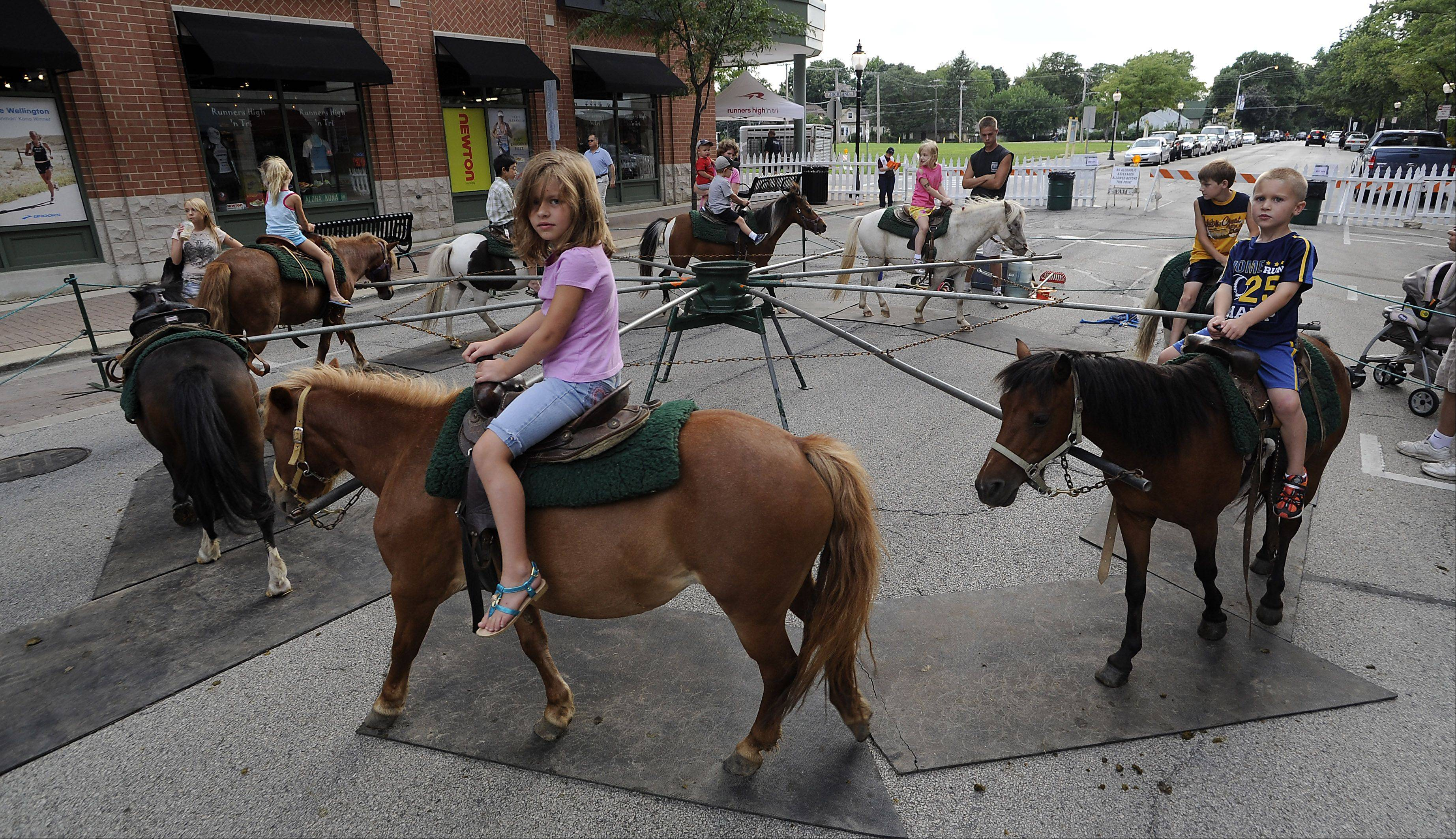 Haley Ferguson, 7, of Mount Prospect goes round and round on a pony at the Mane Event on Friday in downtown Arlington Heights.