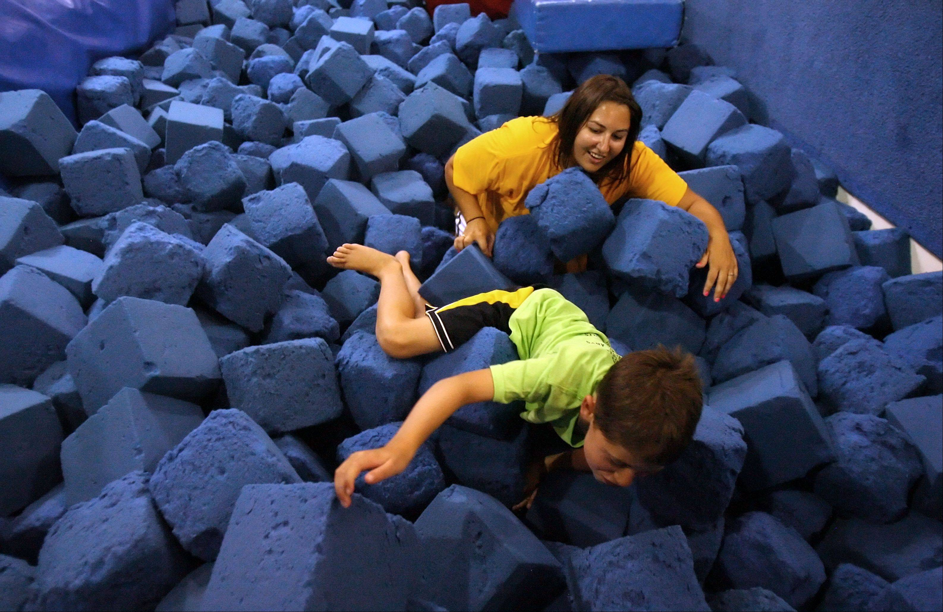 Steve Lundy A foam pit makes great therapy for Colin Brown, 8 of Arlington Heights as he works with occupational therapist Melissa Deets of Greendale, Wis., in a program called A Big Blast Project at the Gym Spot in Mundelein. The program uses gymnastics as therapy for kids with developmental issues.