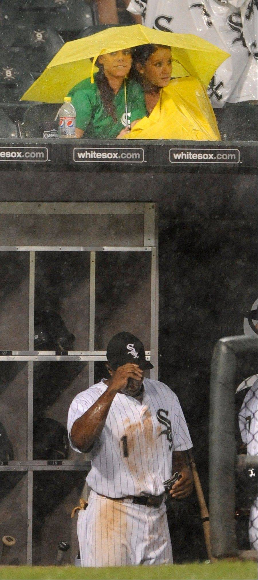 Juan Pierre waits out the rain delay in the dugout while two White Sox fans take shelter Saturday at U.S. Cellular Field.