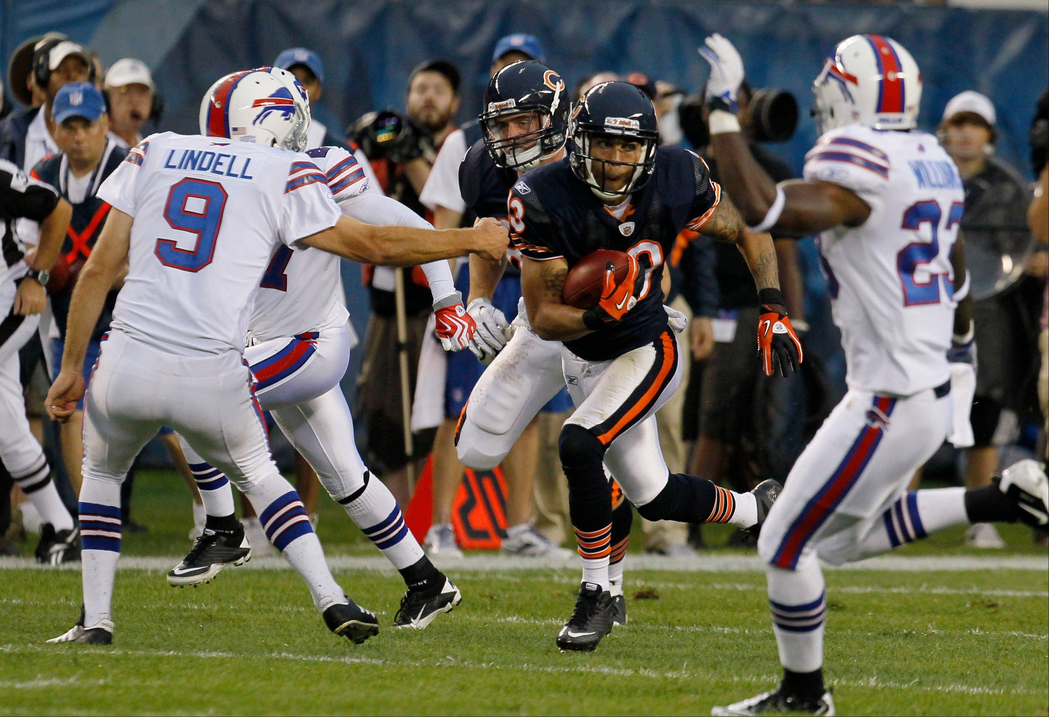 Chicago Bears wide receiver Johnny Knox (13) runs for a 70-yard kickoff return against Buffalo Bills place-kicker Rian Lindell (9) and Aaron Williams (23) in the first half.