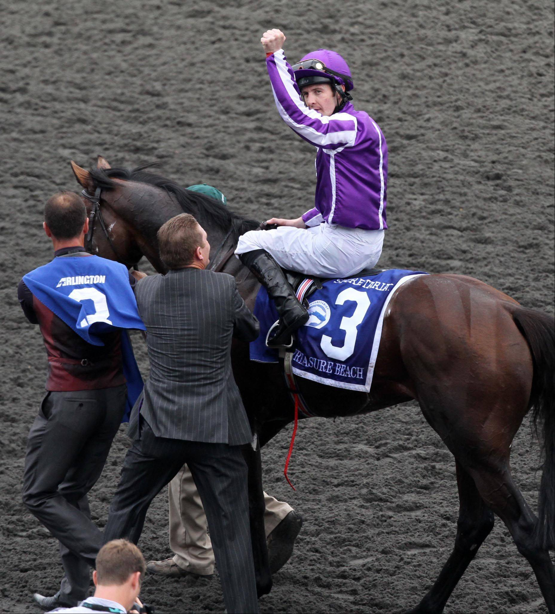 Colm O�Donoghue, aboard Treasure Beach, celebrates victory in the Secretariat Stakes at Arlington Park on Saturday.