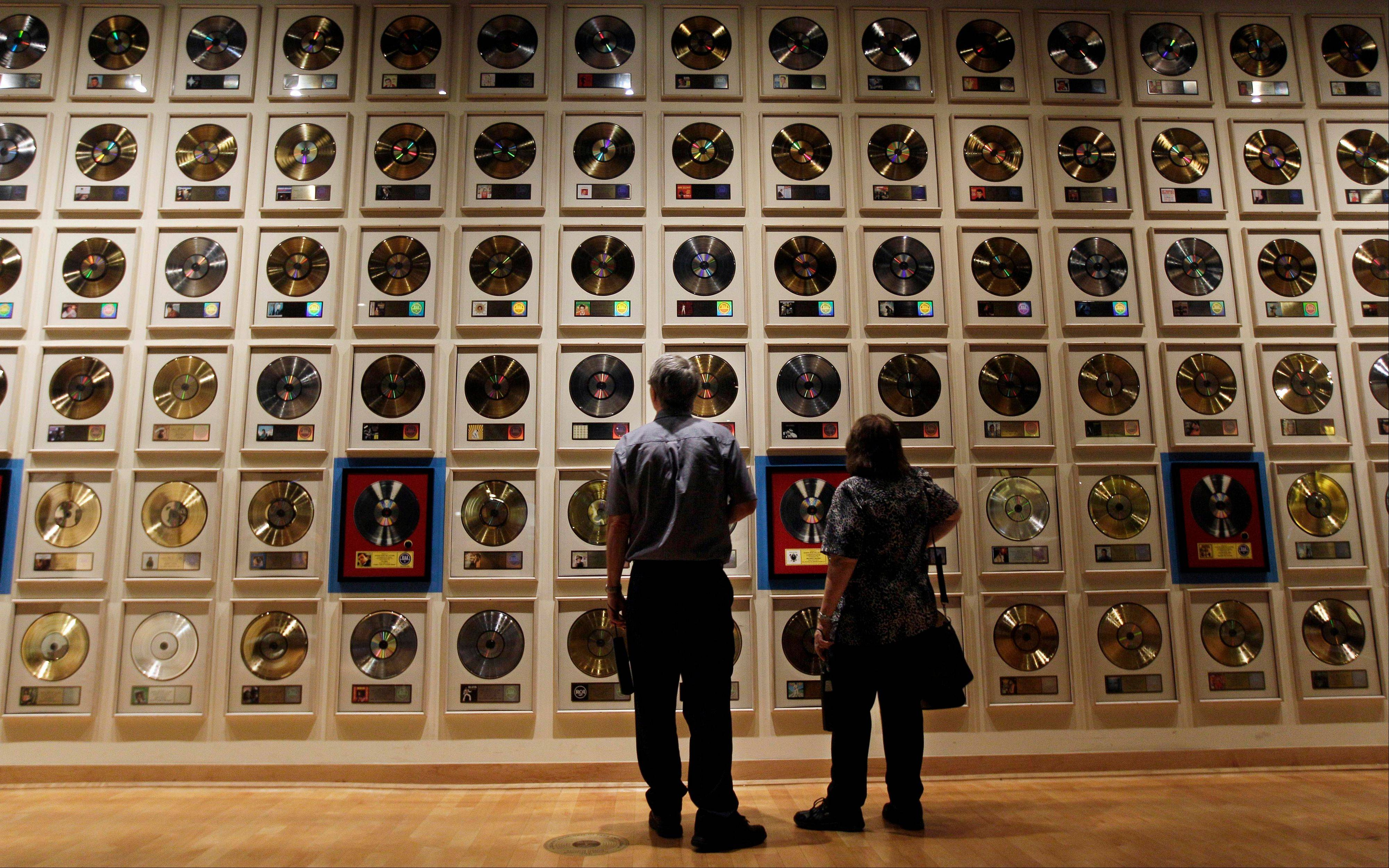 Visitors look over records on display at the Country Music Hall of Fame and Museum in Nashville, Tenn.