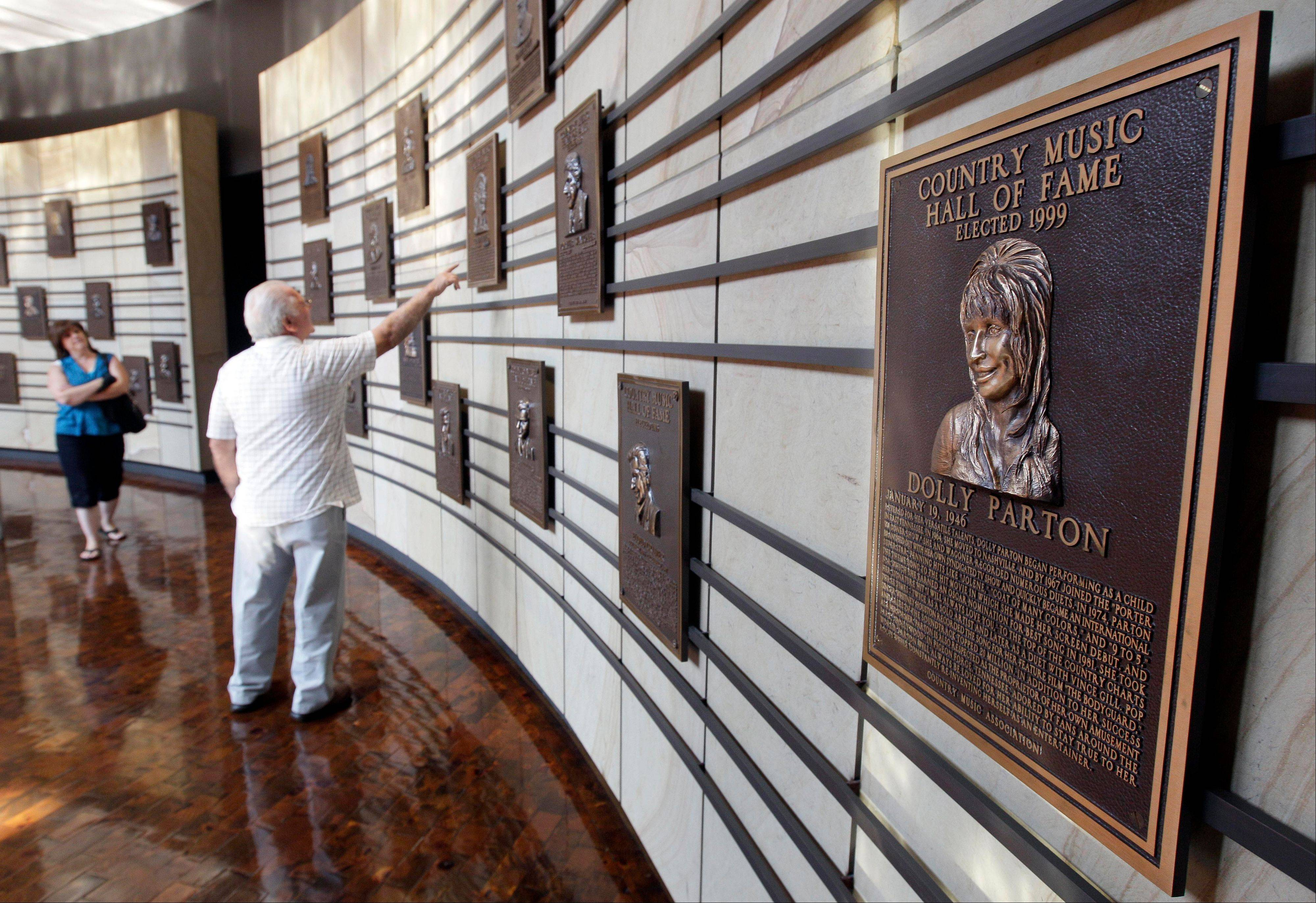 Visitors look at plaques in the Hall of Fame at the Country Music Hall of Fame and Museum in Nashville, Tenn.