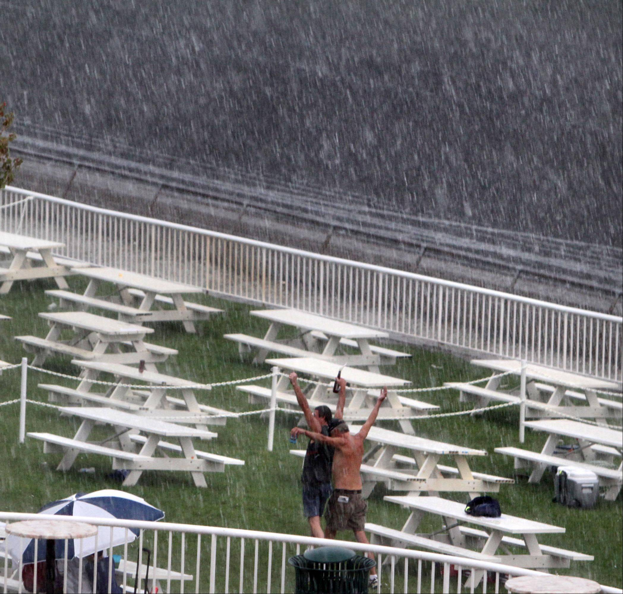 Two men in the picnic area celebrate during the rain delay at Arlington Park on Saturday.