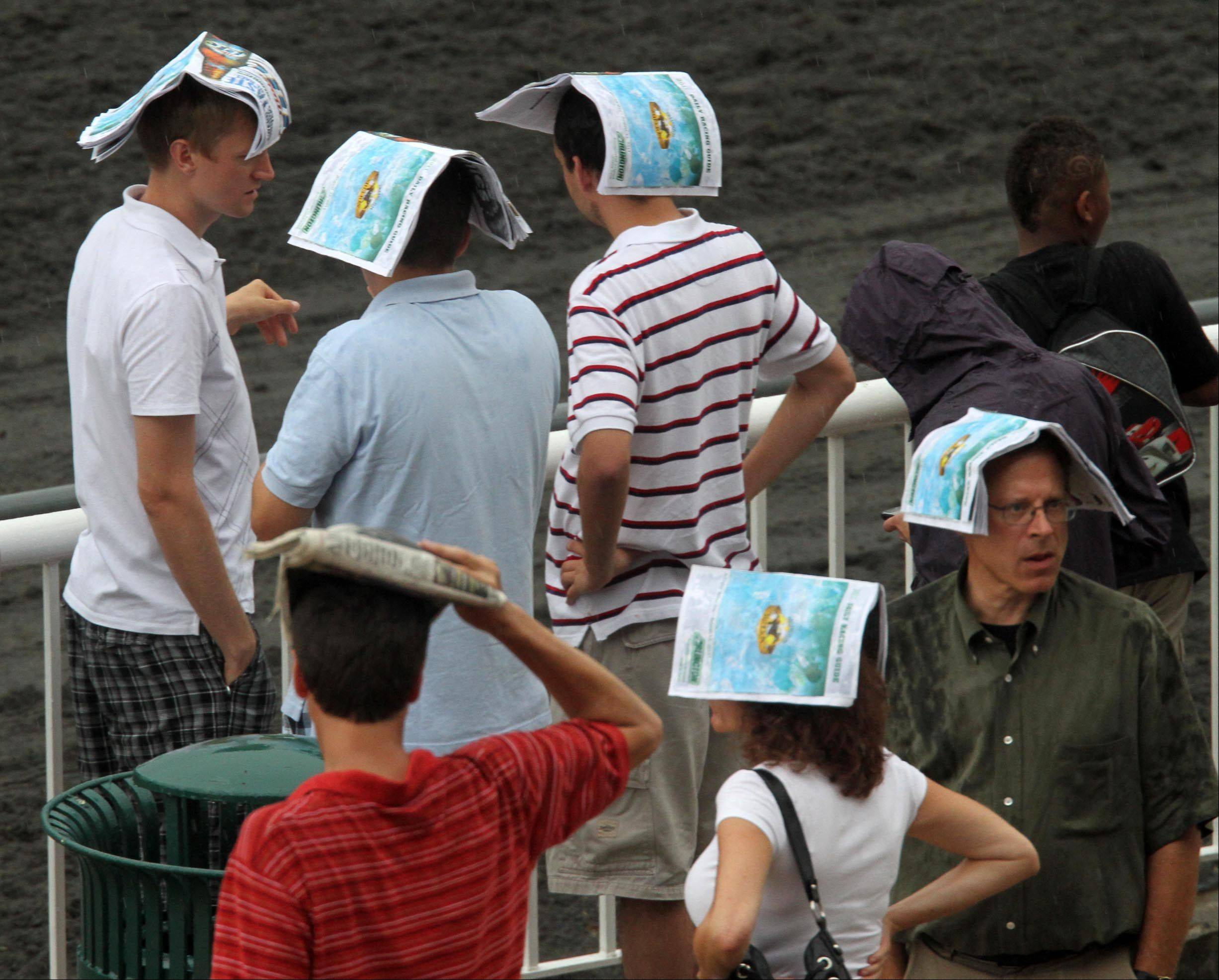 Race fans used their race guide to cover the rain, which fell most of the day at the Arlington Million at Arlington Park on Saturday.