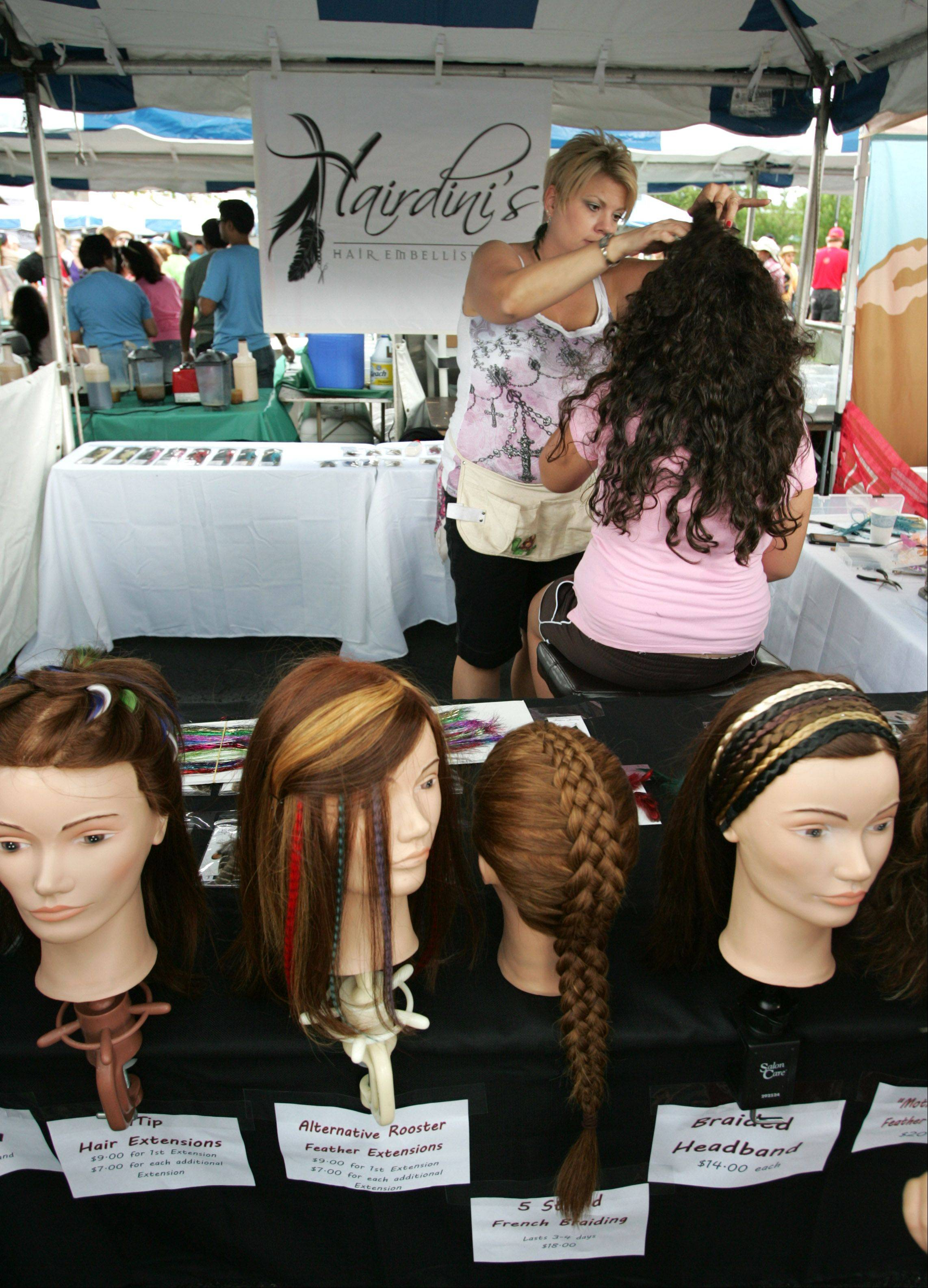 Lynette Pelletier of North Aurora adds hair embellishments Saturday to a customer during Veggie Fest in Naperville. Roughly 100 vendors are on hand for the two-day celebration, many offering organic food delivery, raw food ideas, vegetarian nutrition classes and recipes galore.