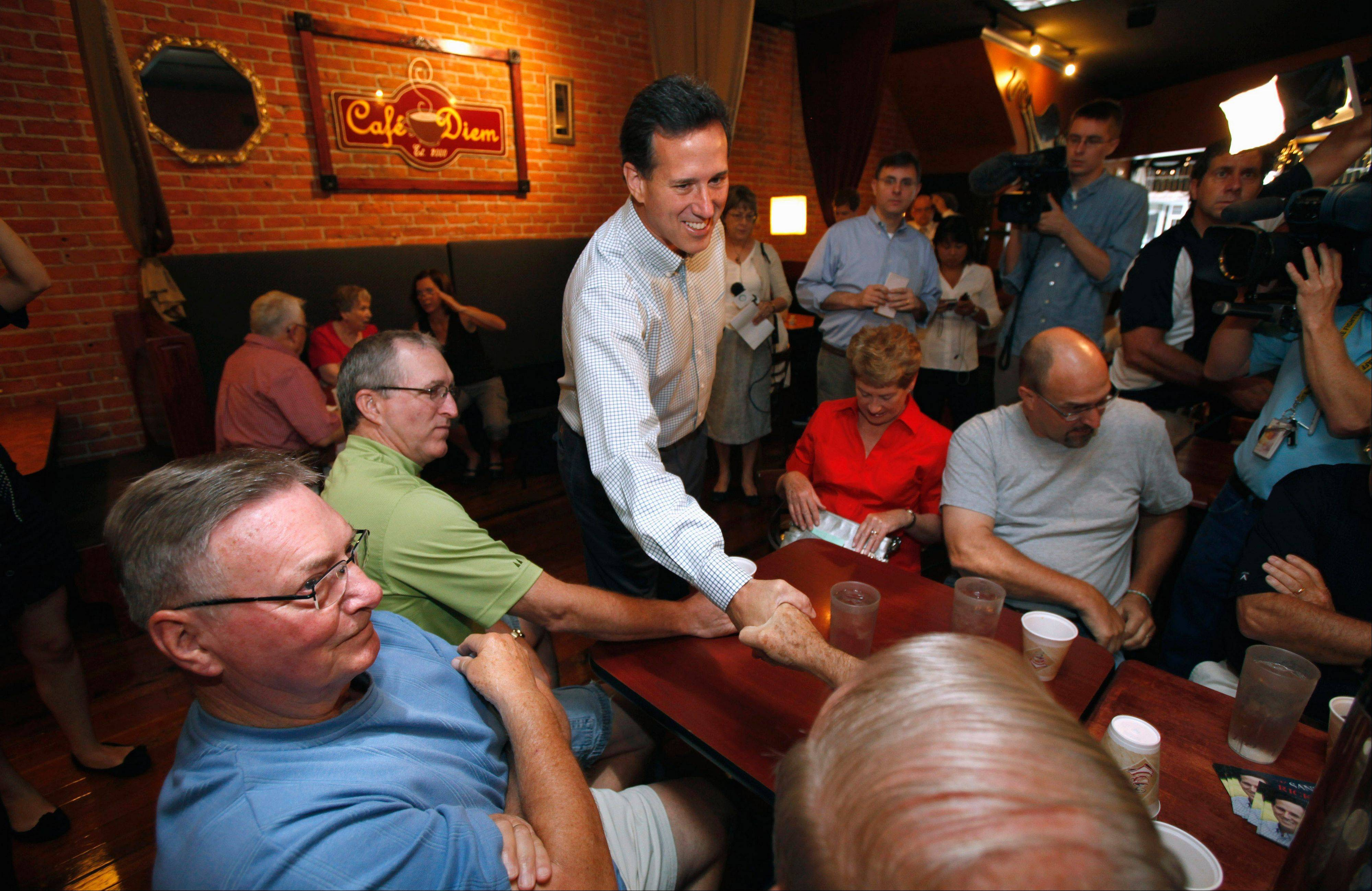 Former Pennsylvania Sen. Rick Santorum, center, greets local residents before speaking in a coffee shop Monday in Ames, Iowa.