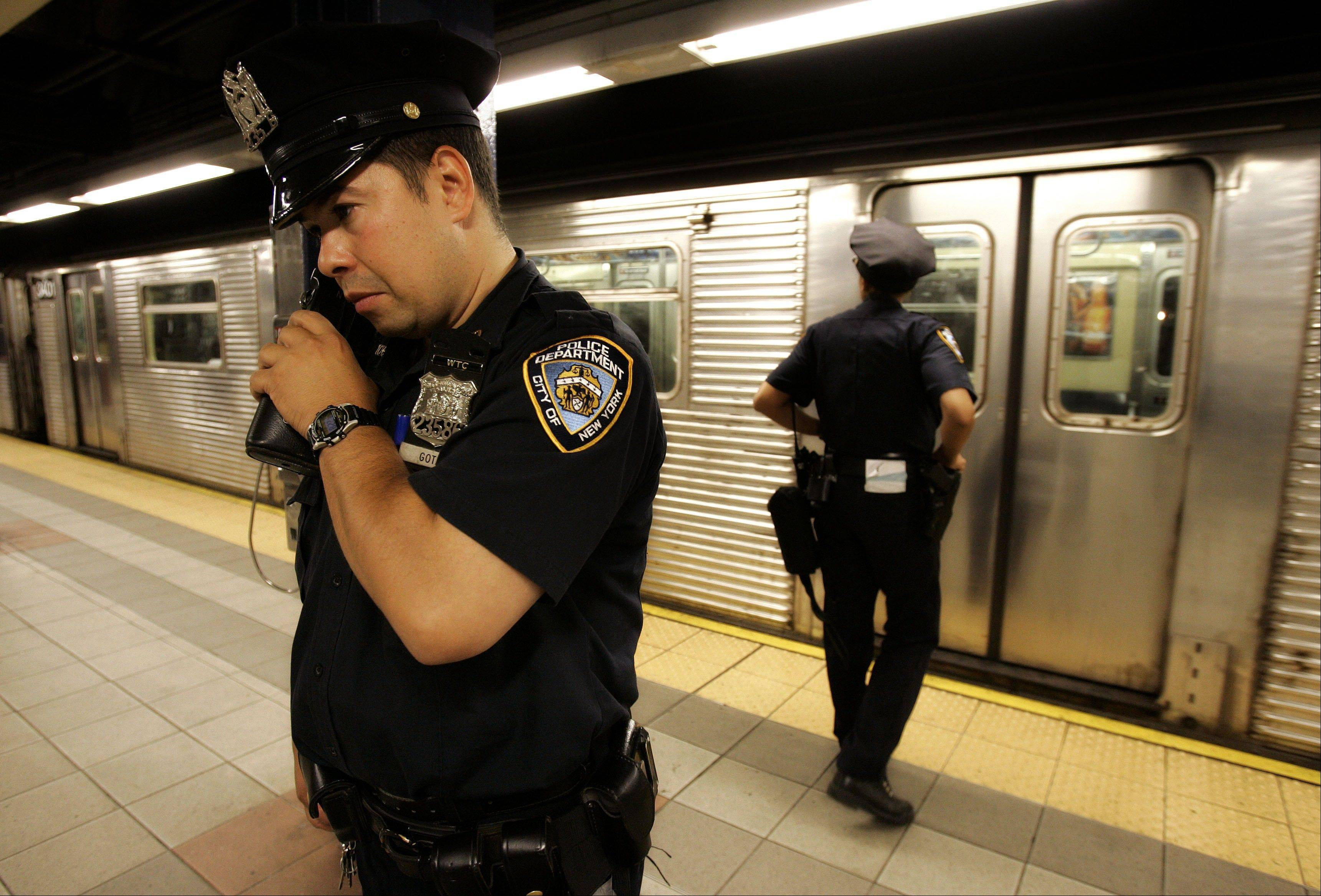 New York police officer Frank Gotay listens to a message on his radio as his partner Yolanda Cortes waits for a subway car's doors to open while performing random checks along the platform at the 42nd Street station in New York.