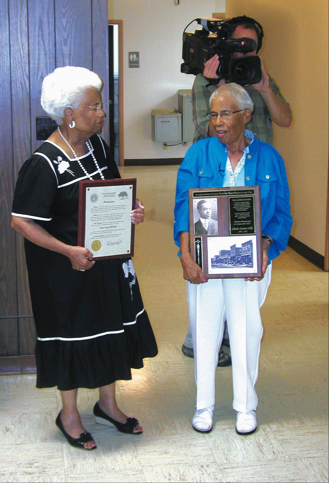 Wilma Ellis Kazemzadeh, left, and Adrienne Ellis Reeves accept a plaque in honor of their father, Charles Everett Ellis, on July 31 in Altamont, Ill. Behind the sisters, Michael Wunsch is shooting footage for an upcoming documentary centered around a diary that Charles Ellis kept for more than 40 years.