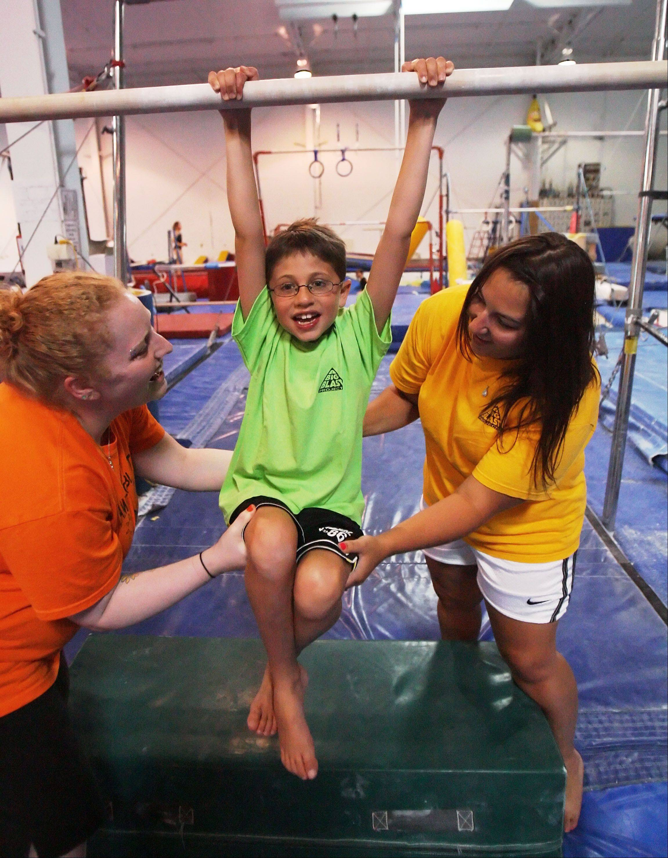Steve LundyJanet Wadkins, left, director of A Big Blast Project and occupational therapist Melissa Deets help Colin Brown, 8 of Arlington Heights work on the uneven bars at the Gym Spot in Mundelein. The program uses gymnastics as therapy for kids with developmental issues.