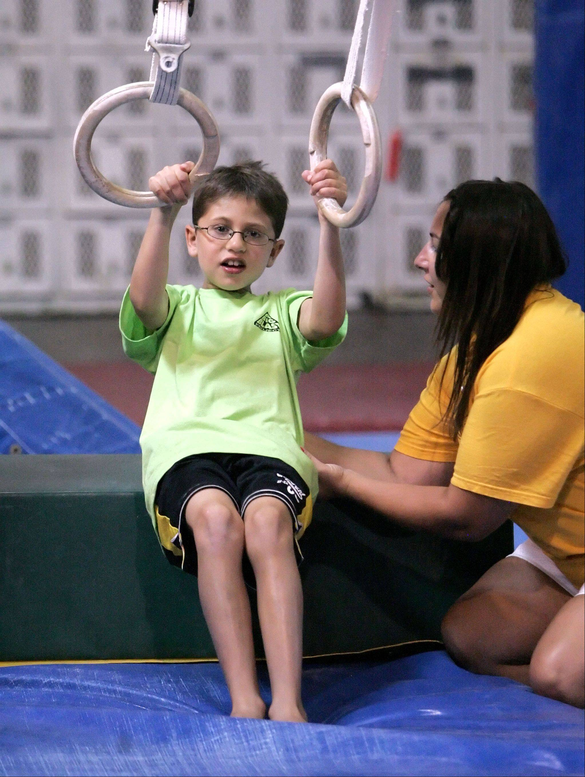 Steve LundyColin Brown, 8 of Arlington Heights, left, works on the rings with occupational therapist Melissa Deets of Greendale, Wis., at the Gym Spot in Mundelein as part of A Big Blast Project. The program uses gymnastics as therapy for kids with developmental issues.