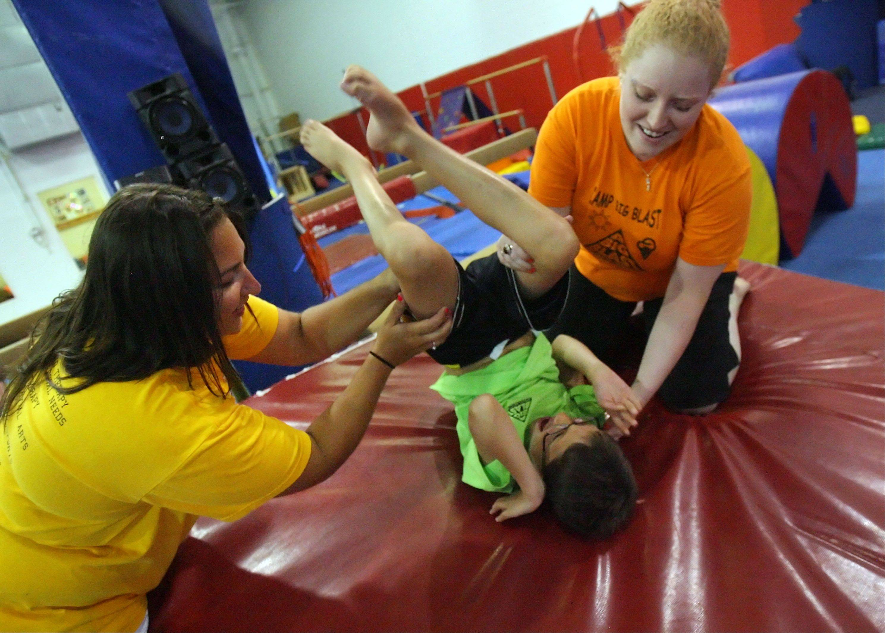 Steve LundyJanet Wadkins, left, director of A Big Blast Project and occupational therapist Melissa Deets help Colin Brown, 8 of Arlington Heights do a backward roll at the Gym Spot in Mundelein.