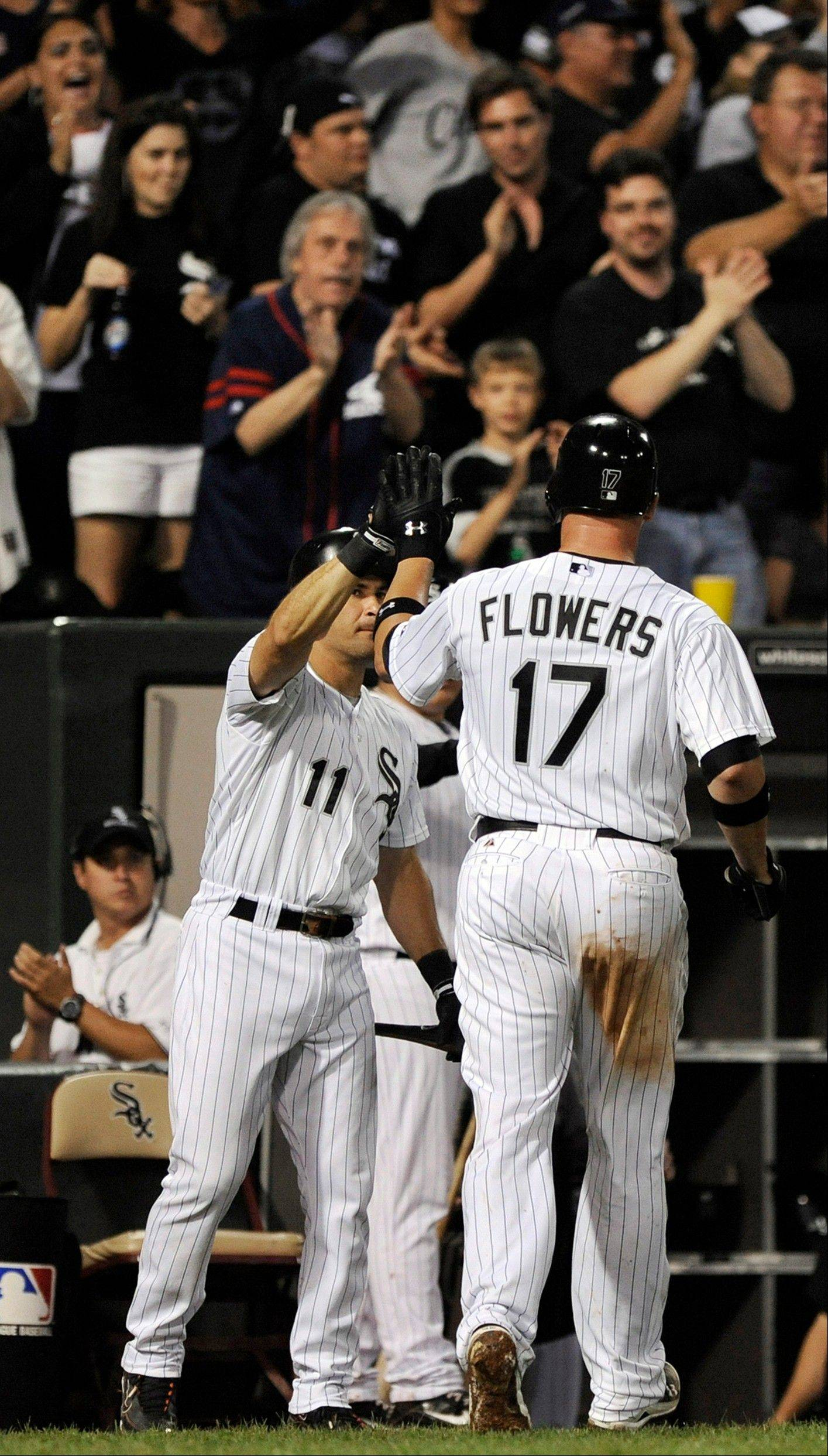 Chicago White Sox's Tyler Flowers right, celebrates with teammate Omar Vizquel after hitting a solo home run against the Kansas City Royals during the fifth inning of a baseball game in Chicago, Saturday, Aug. 13, 2011.