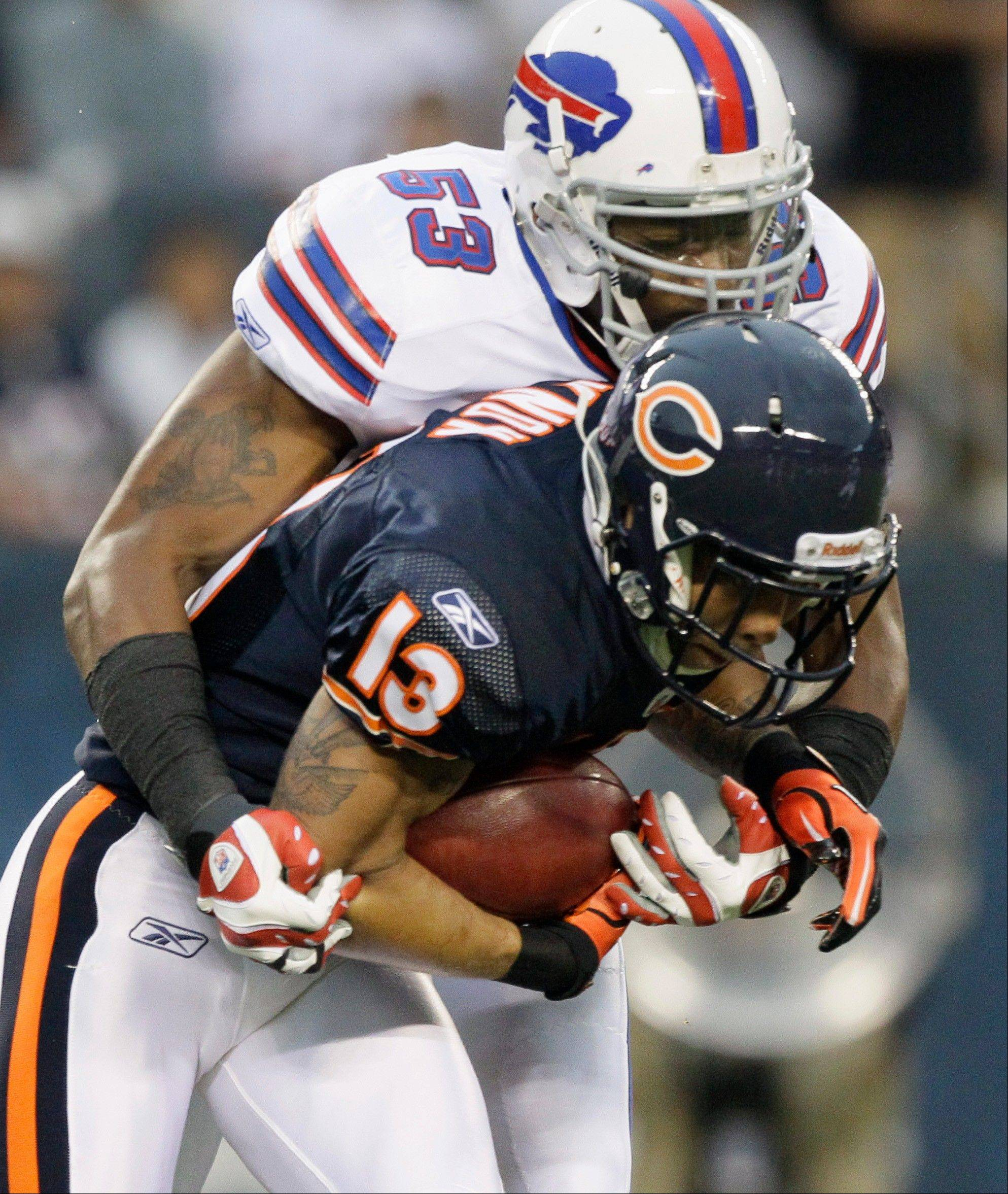 Johnny Knox is tackled by Buffalo Bills linebacker Reggie Torbor in the first half Saturday night at Soldier Field.