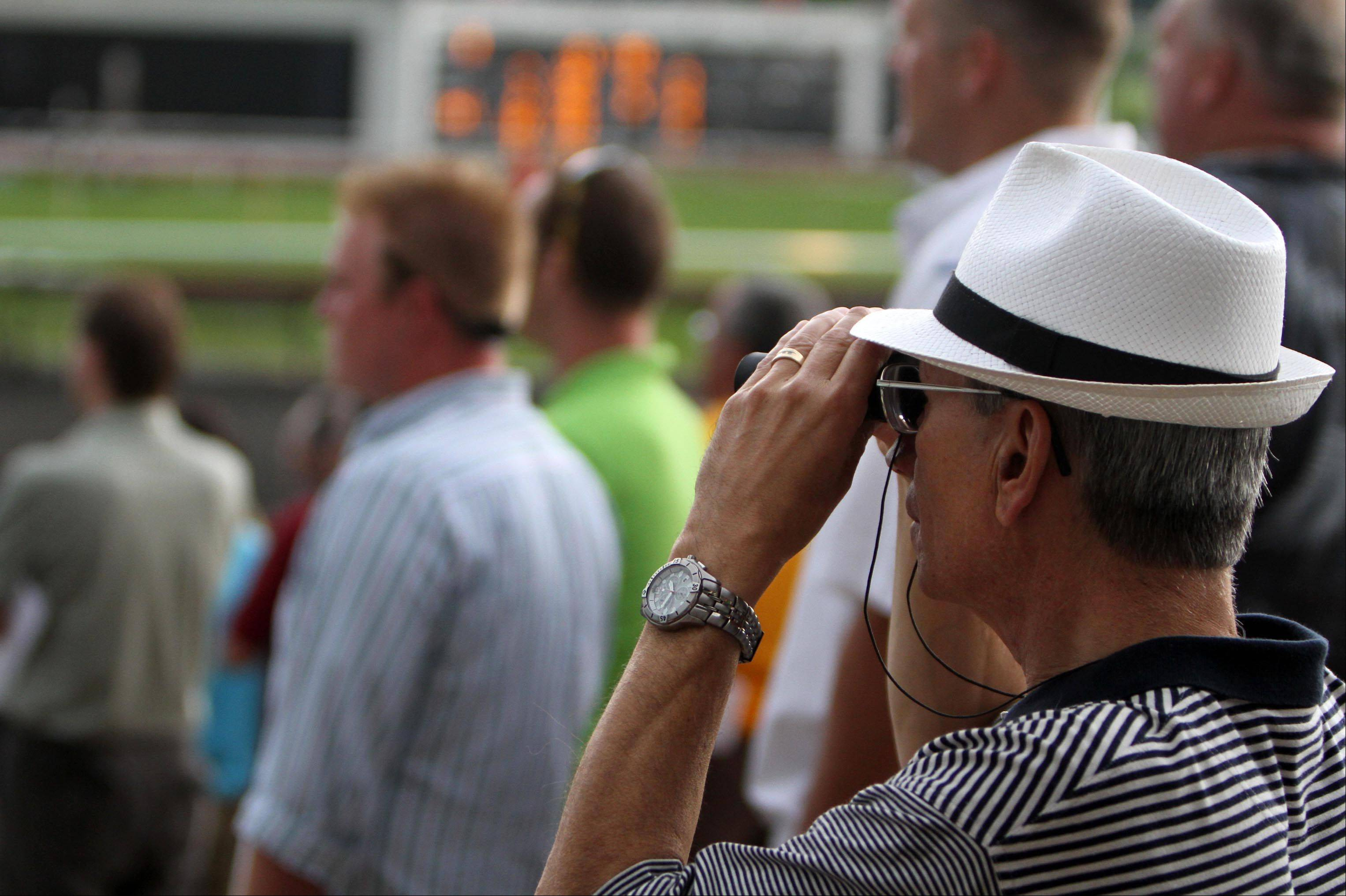 Al Hall of Arlington Heights takes a close look at an early race at Arlington Park on Saturday.