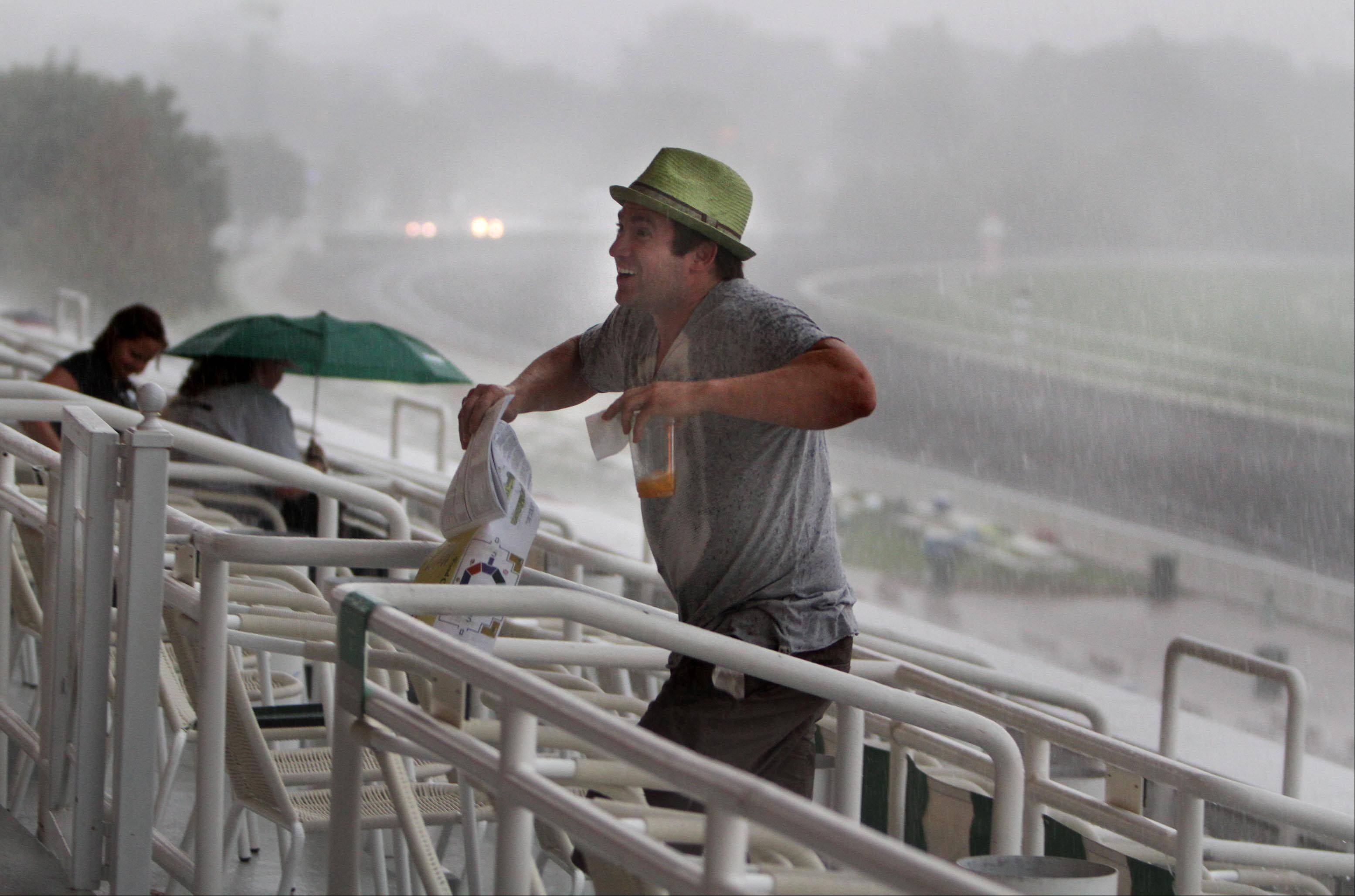 Rory McKenna of Arlington Heights runs for cover as it rains heavy before the Arlington Million at Arlington Park on Saturday.