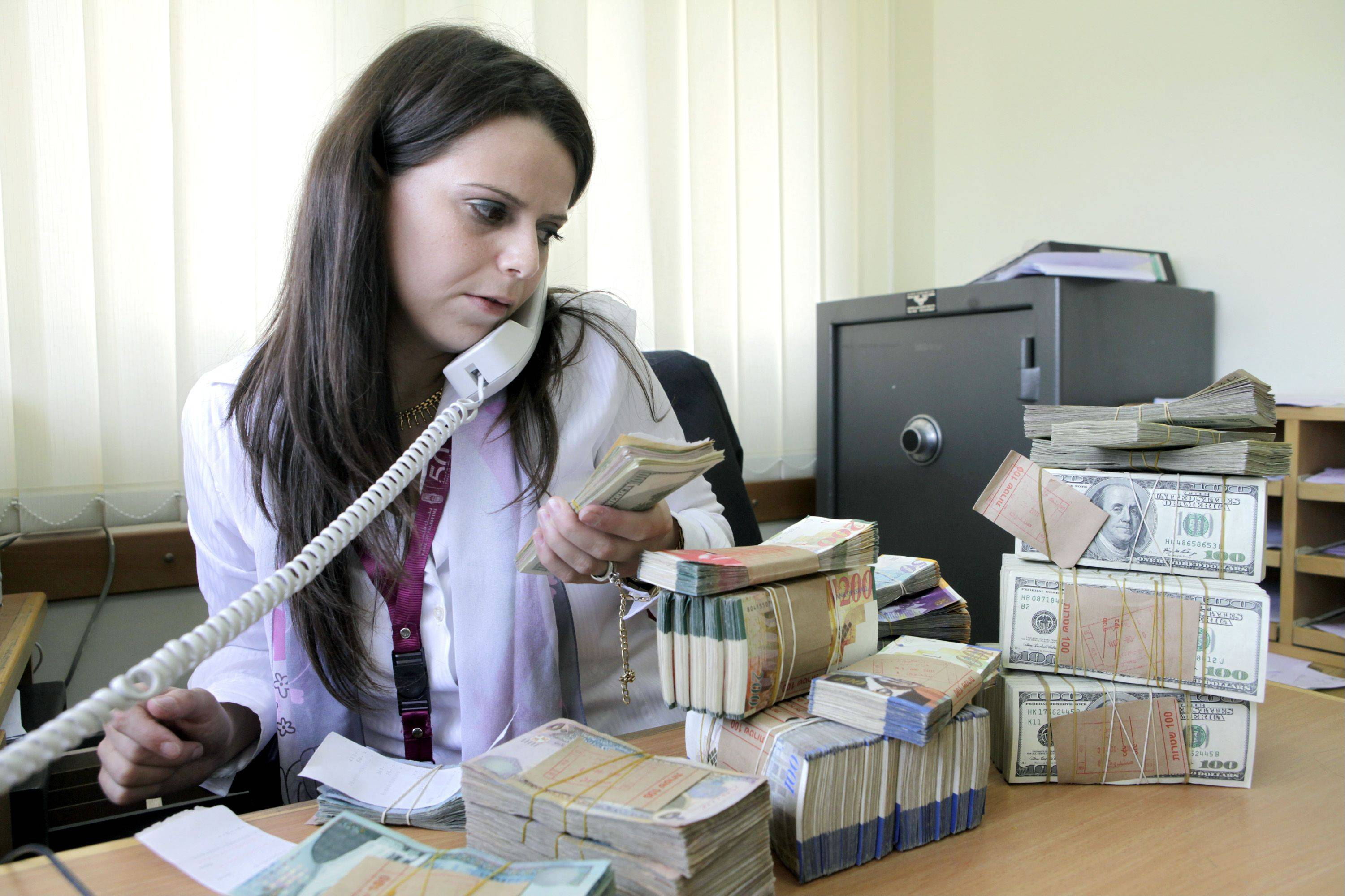 Reem Qaraqe, a teller at the Bank of Palestine Plc, counts U.S. dollars at her desk in a branch of the bank in Bethlehem, West Bank. By winning the confidence of her customers, Qaraq is helping to fulfill the vision of the Bank of Palestine�s 35-year-old CEO, Hashim Shawa.