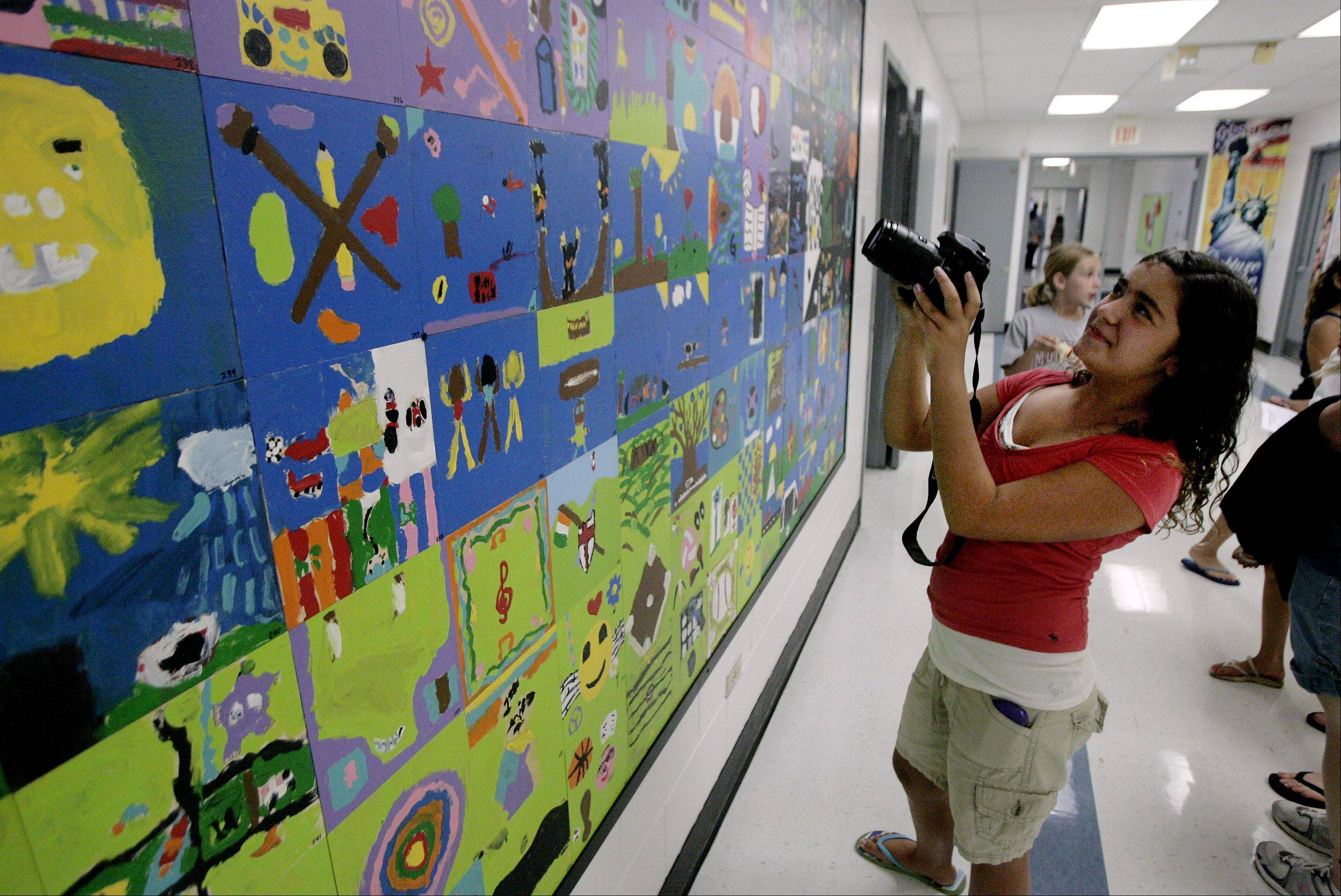 Brianna Dufault, 11, takes a picture of the tile she created in the mural during a back-to-school open house Sunday at Mechanics Grove School in Mundelein. This year, the school will combine Lincoln and Mechanics Grove schools and become a third- through fifth-grade building.
