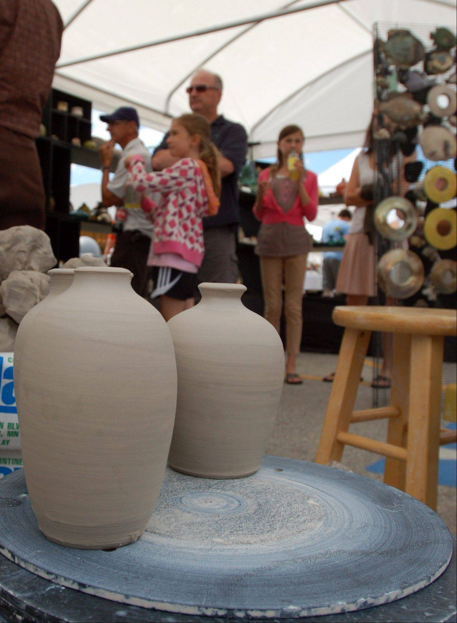 Raku Gold Pottery was a popular booth to visit Sunday during the 7th annual Art in Your Eye fine art show in Batavia. The artists of Raku Gold, Shawn and Jim Barbagallo of Rockford, displayed several ceramic pieces, created using the Japanese technique called Raku.