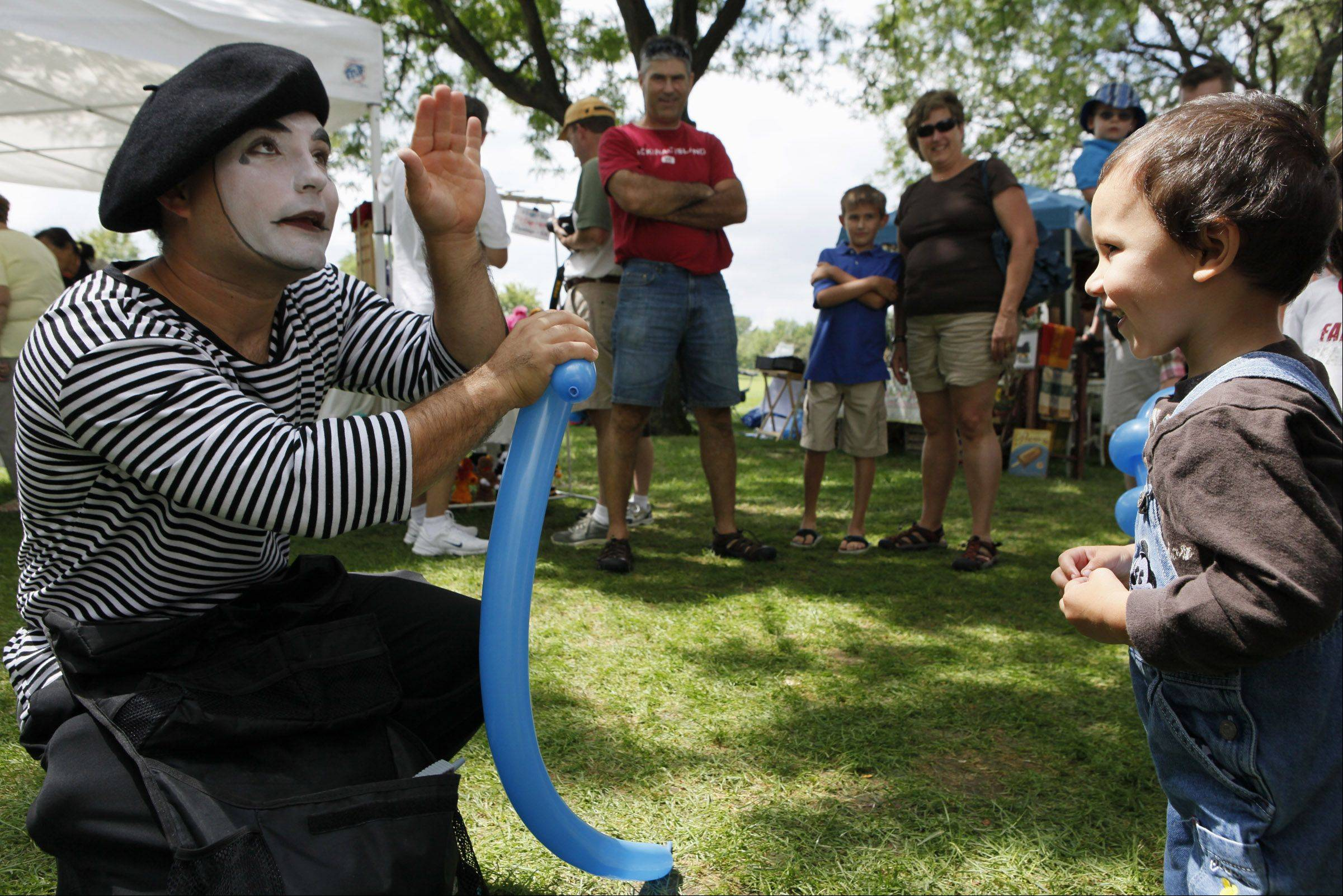 A mime makes a balloon gun for Ronan Mendoza, 2, during the Cantigny Park�s French Connection Day Sunday in Wheaton.