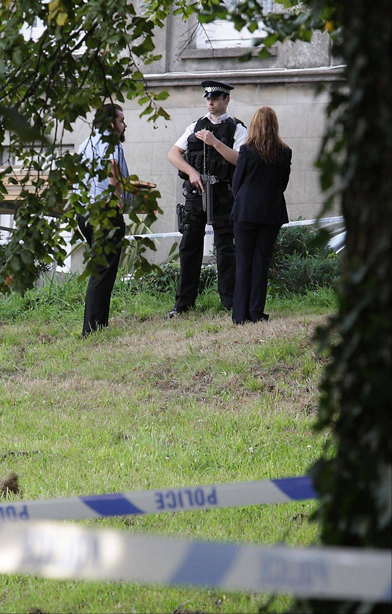 People talk to a British armed policeman attending the scene after six people were killed in a knife attack, Sunday Aug. 14, 2011, in St Helier, Jersey, England. A man is reported to have been arrested Sunday on suspicion of fatally stabbing six people, including two young children, two men and two women, on the British island of Jersey, police said, and unidentified neighbors declared that the incident may have involved members of the same family.