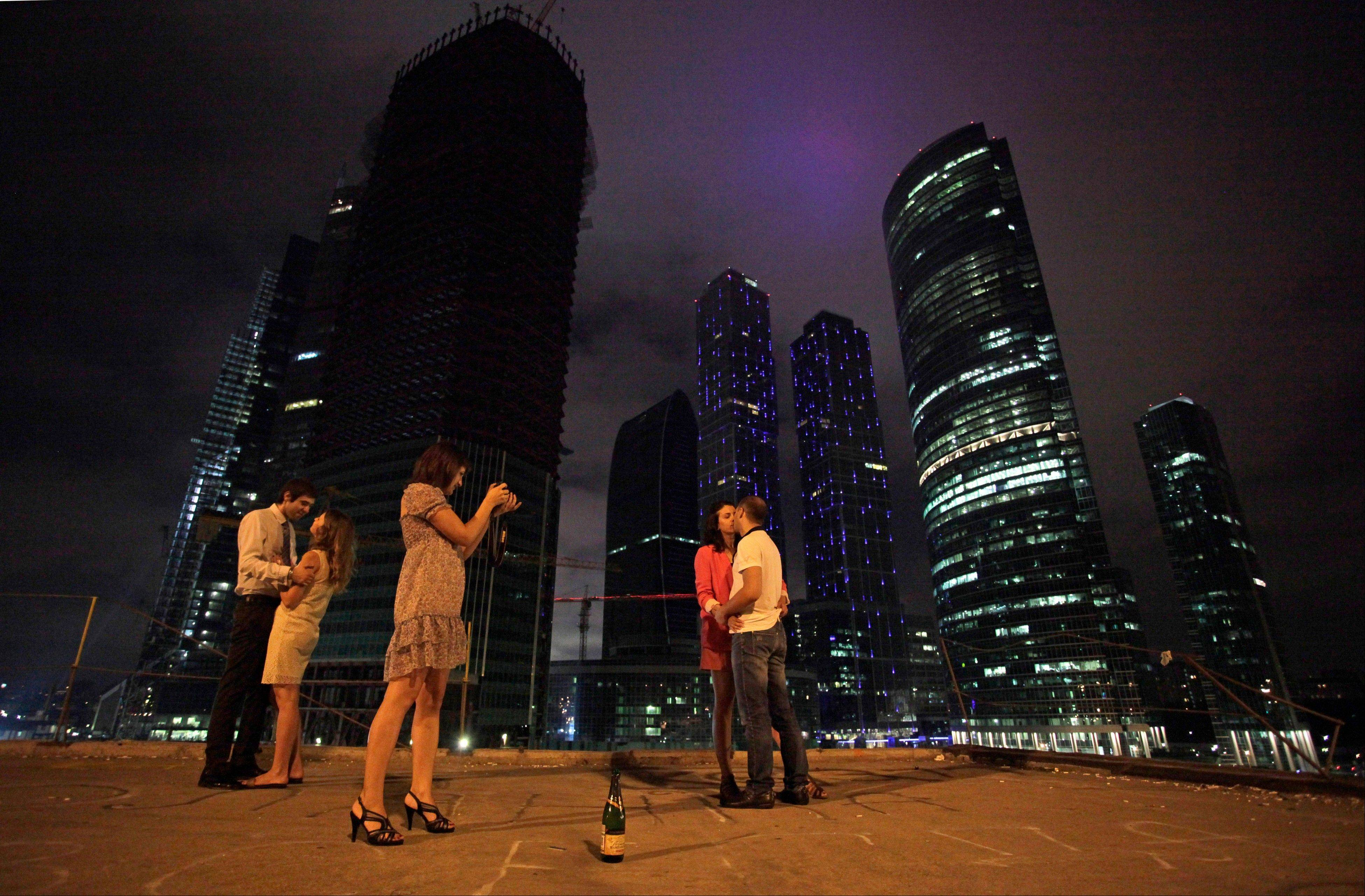 Youths stand in front of Moscow�s City Center skyscrapers in Moscow, Russia. In the 20 years since the collapse of the Soviet Union, the once shabby and dour Russian explosion has exploded with wealth and glitzy developments.