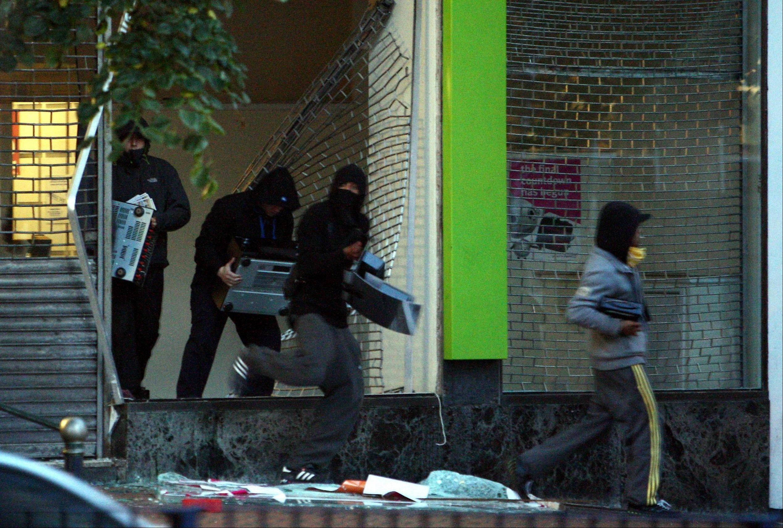 Youths run from an electronics store in Birmingham, England as disturbances saw looting and vehicles set alight. As Britain comes to grips with the causes of the past week�s descent into anarchy, Prime Minister David Cameron has identified the growth of gangs as a key factor and is recruiting high-profile American anti-gang experts to help bring them to heel.