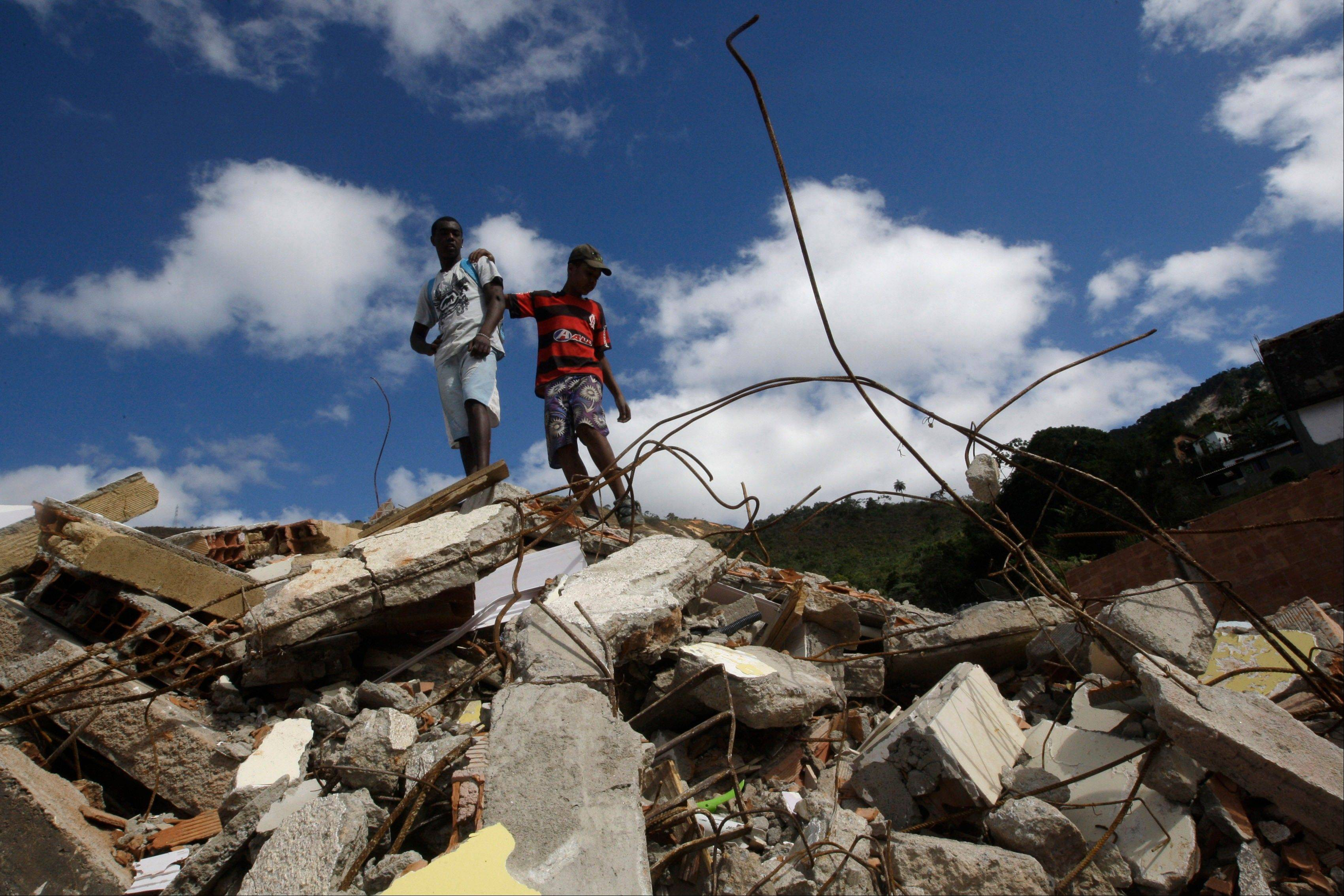 Julio Cesar, 18, left, and friend Vitor, 14, stand on the debris of Cesar�s house, destroyed by a January mudslide, in Teresopolis, Brazil.