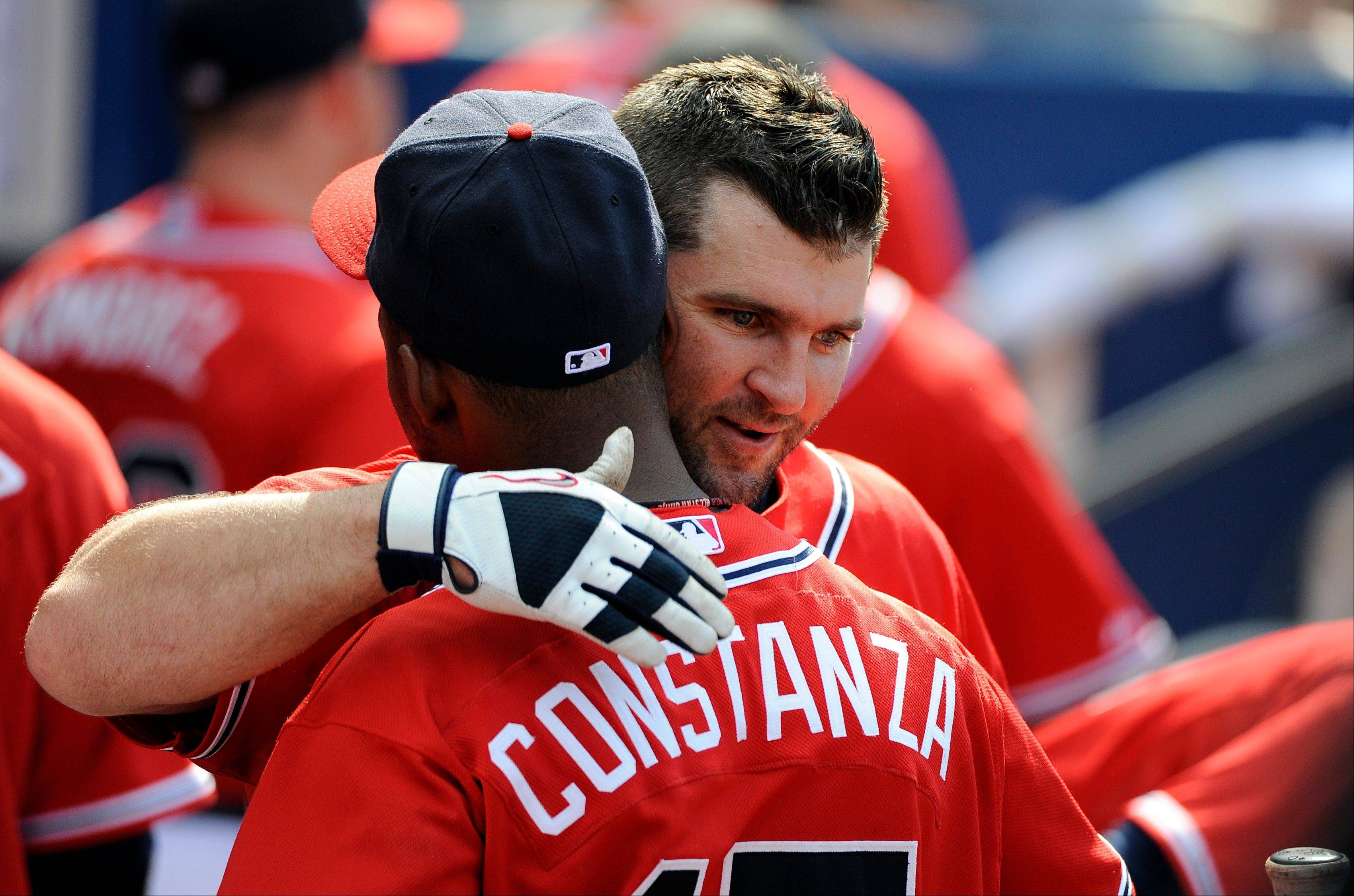 Atlanta�s Dan Uggla gets a hug from teammate Jose Costanza in the dugout Sunday after Uggla�s 33-game hitting streak came to an end. He went 0-for-3 in the Braves� loss to the Cubs.