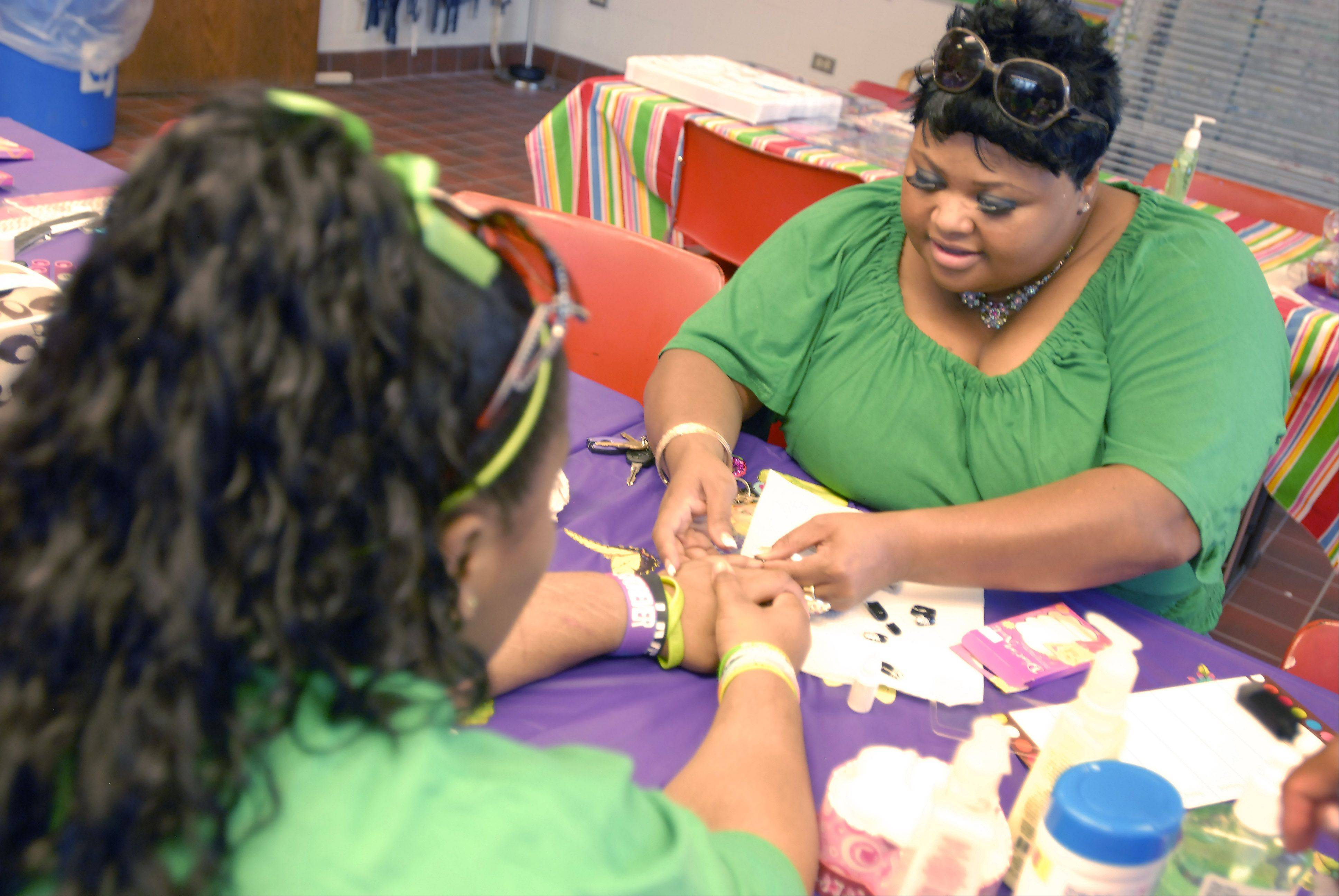 April Momon, evening supervisor at Maryville's Casa Imani group home in Bartlett for pregnant girls and young moms, decorates a teen's nails during Family and Friends Day.