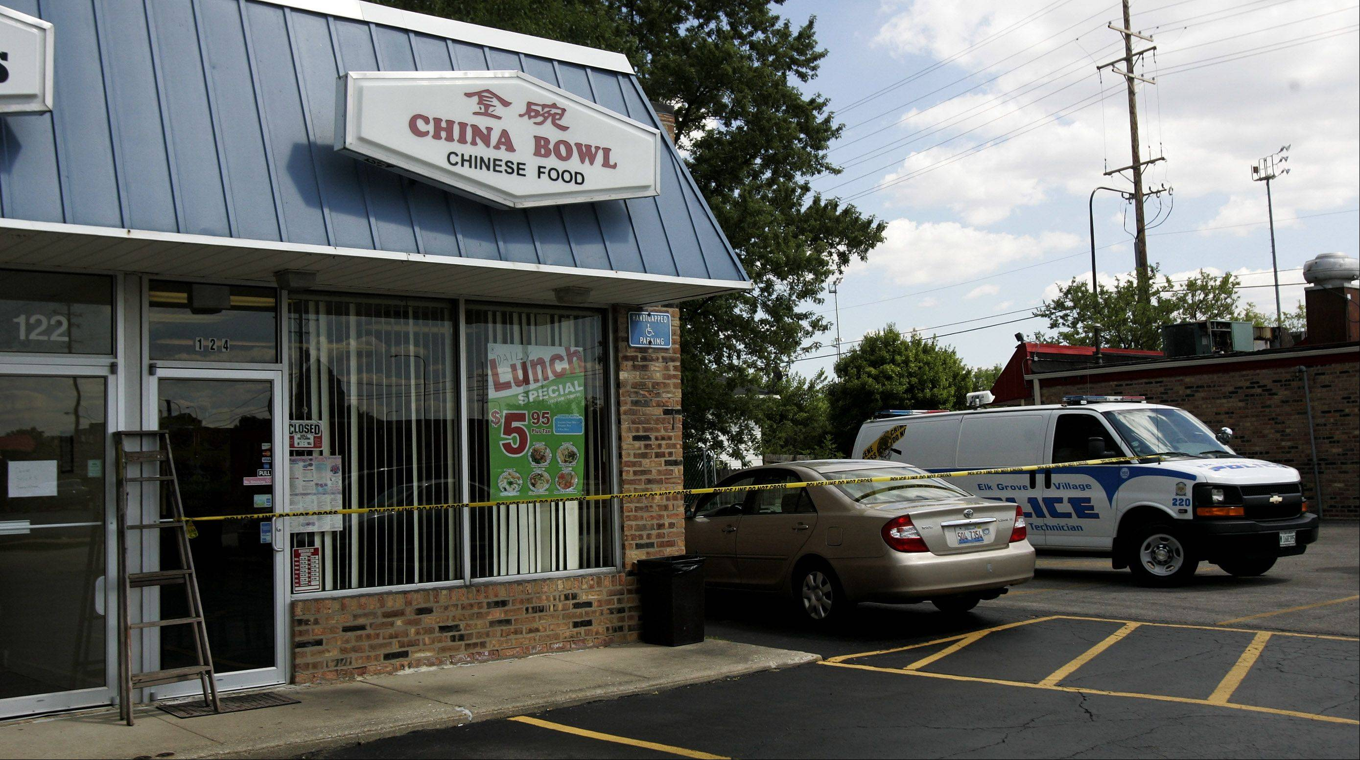 Elk Grove Village police investigate the scene where three people were injured during a fight behind a Chinese restaurant in the Turner Plaza strip mall Monday afternoon. Authorities said one man is in custody.