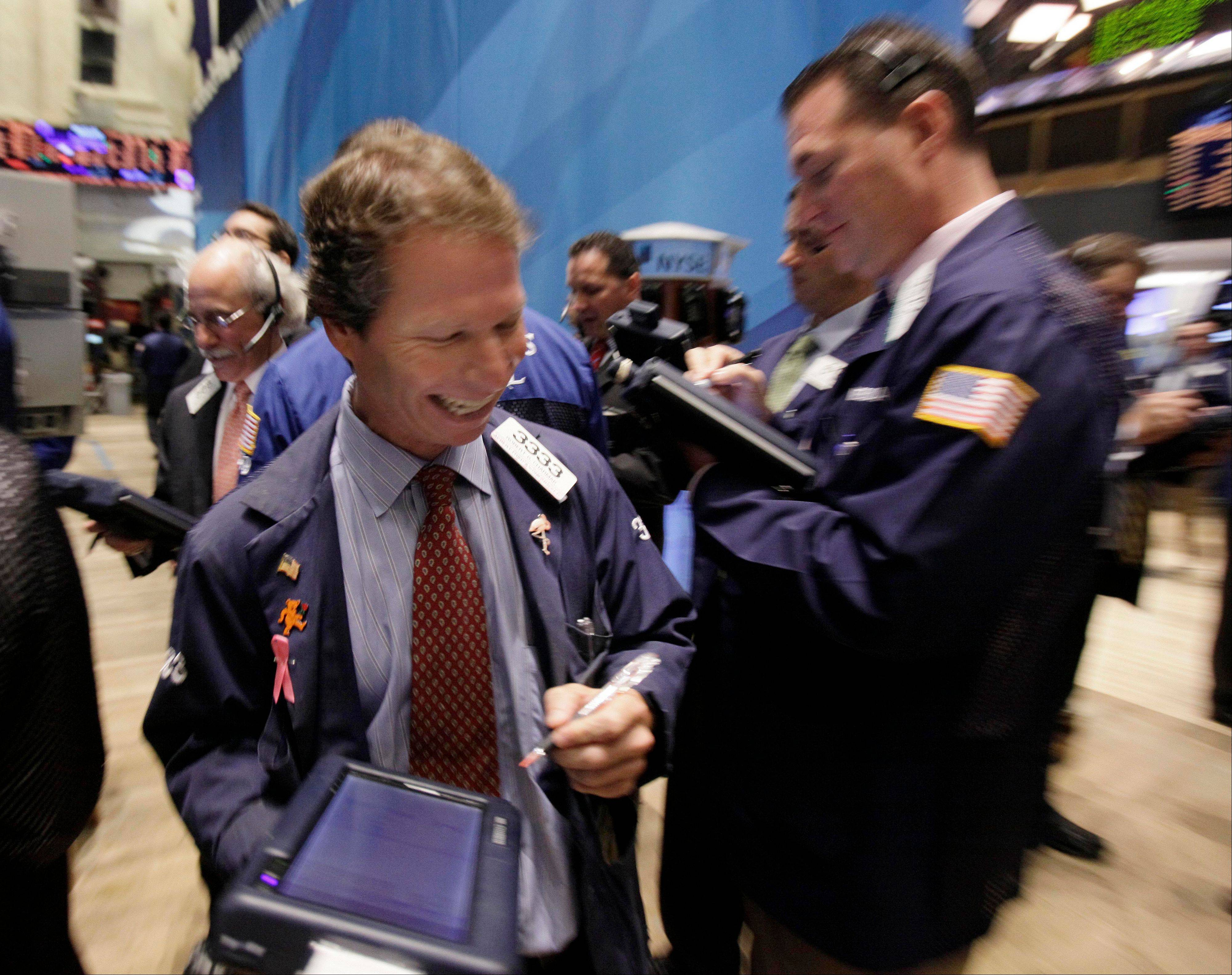 Trader Robert Charmak, center, works Monday on the floor of the New York Stock Exchange.
