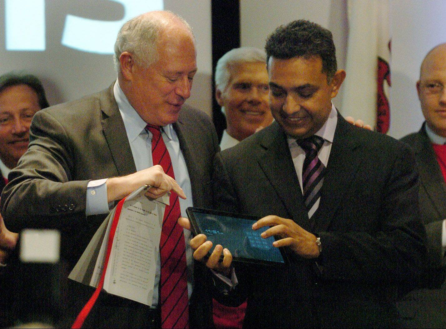 Illinois Gov. Pat Quinn and Motorola Mobility Chairman and CEO Dr. Sanjay Jha, right, look at the Motorola XOOM tablet in May after announcing that the Motorola Mobility Inc. corporate headquarters would be located in Libertyville.