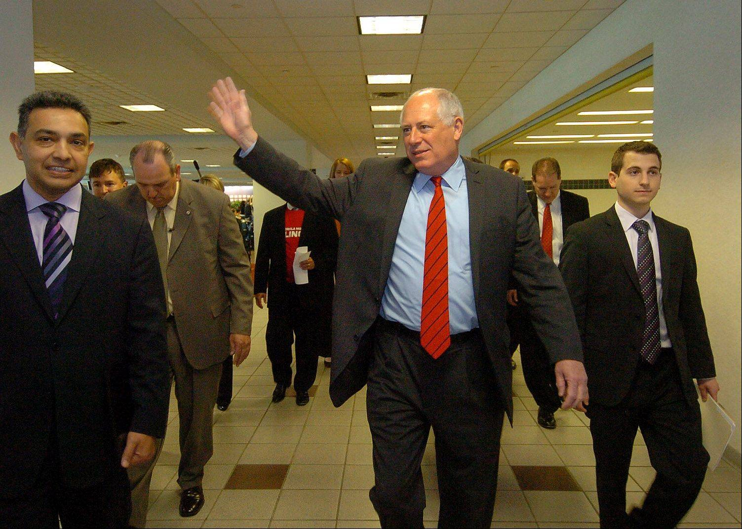 Illinois Gov. Pat Quinn waves to employees of Motorola Mobility in May after making an announcement with Motorola Mobility Chairman and CEO Dr. Sanjay Jha, left, that the company would stay headquartered in Libertyville.