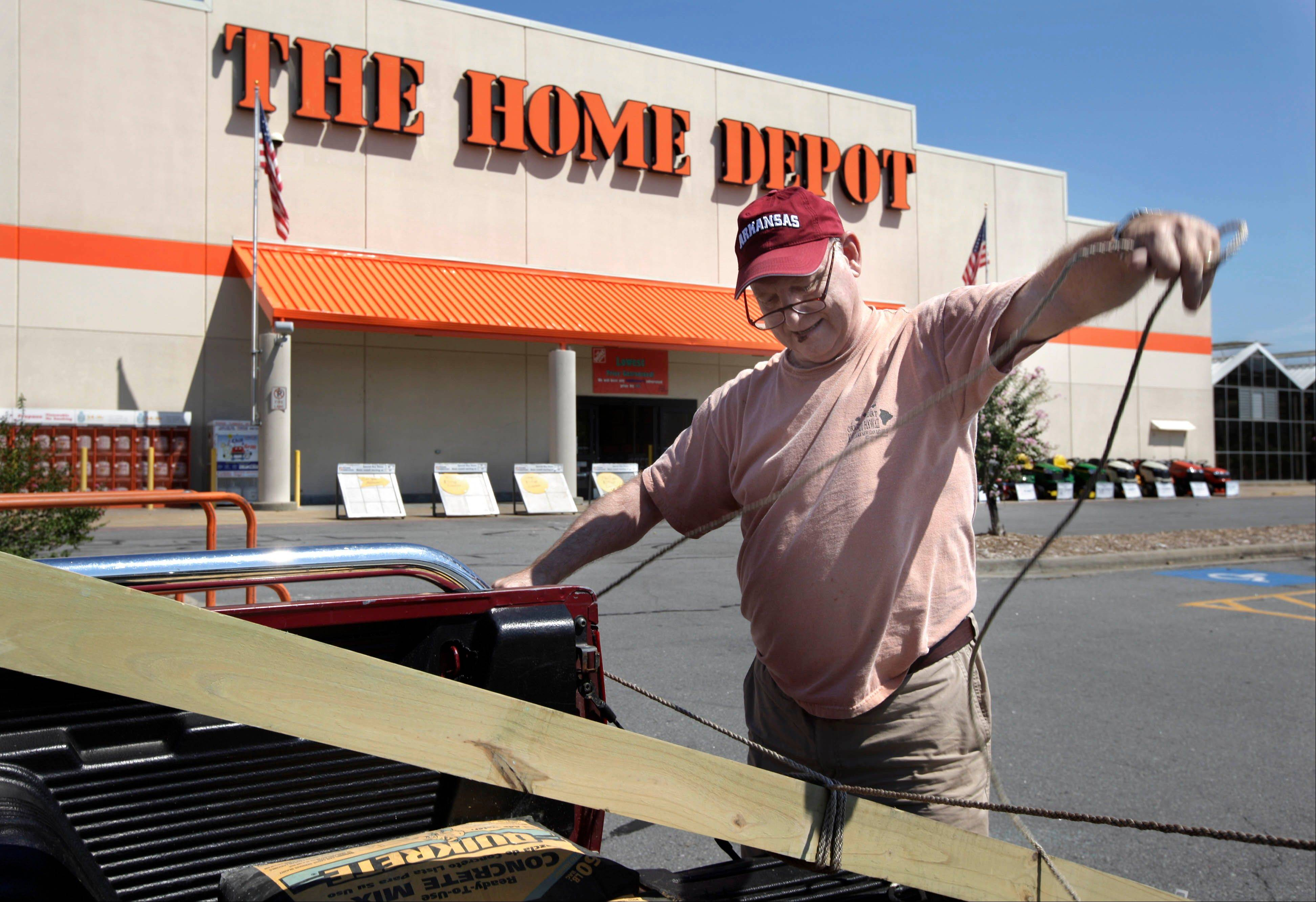 Tom Malone lashes building materials down to his truck at a Home Depot store in North Little Rock, Ark.
