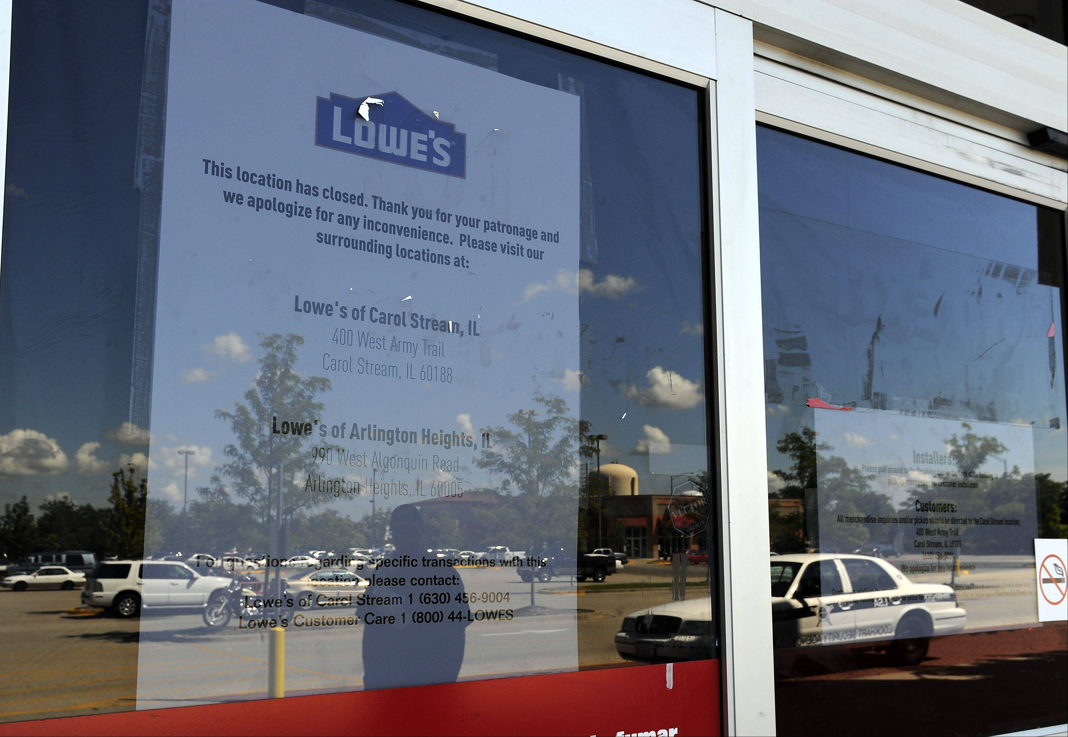 The reflection of security officer Terry Green and the store closing sign were that was left on the facade of the Lowe's in Schaumburg on Monday, one day after employees learned the store was one of seven being closed nationwide by the home improvement chain.