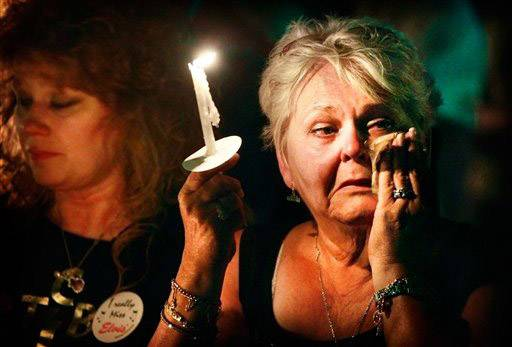 "Charlotte Stone of Griffin, Ga., wipes tears from her eyes as the song ""Can't Help Falling In Love"" is played during a candlelight vigil Monday night marking the 34th anniversary of the death of Elvis Presley at Graceland in Memphis."