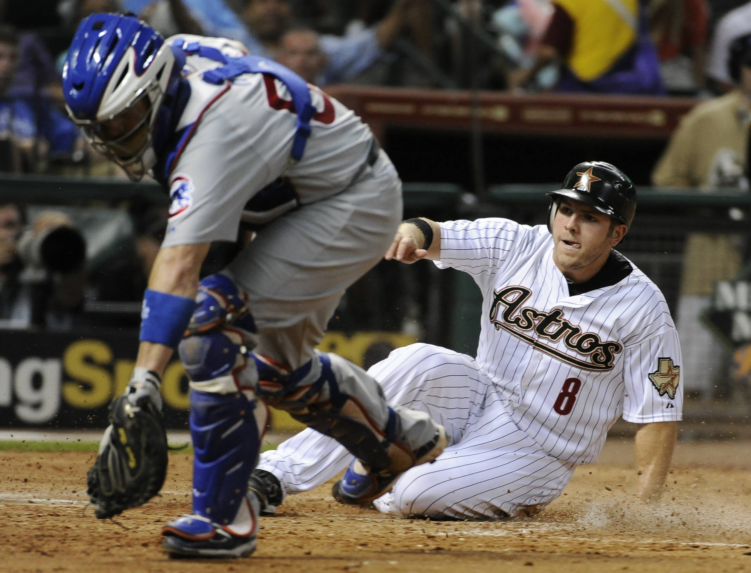 Houston Astros' J.B. Shuck (8) slides into home plate as Chicago Cubs catcher Koyie Hill chases the ball Tuesday during the seventh inning in Houston. Shuck scored from third base on a Humberto Quintero sacrifice fly.