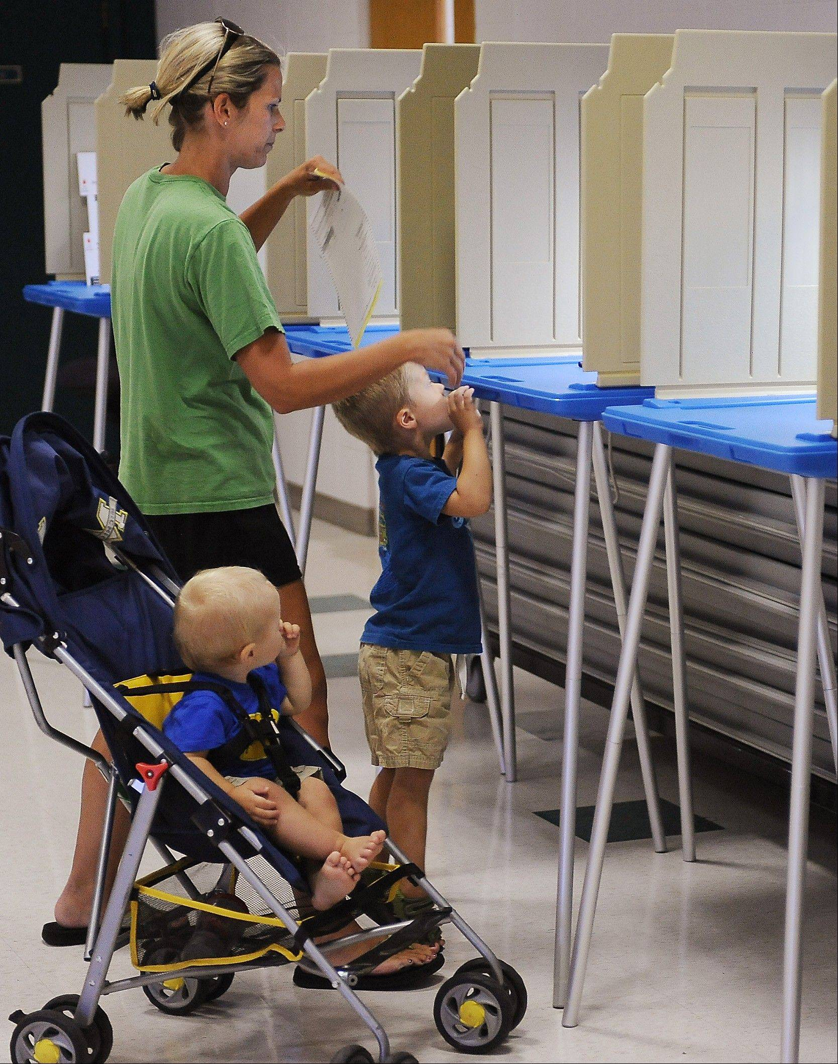 Molly Day takes her sons Brady, 3 and Shane, 11 months, to the voting poll Tuesday at Pleasant Prairie, Wis., Village Hall.
