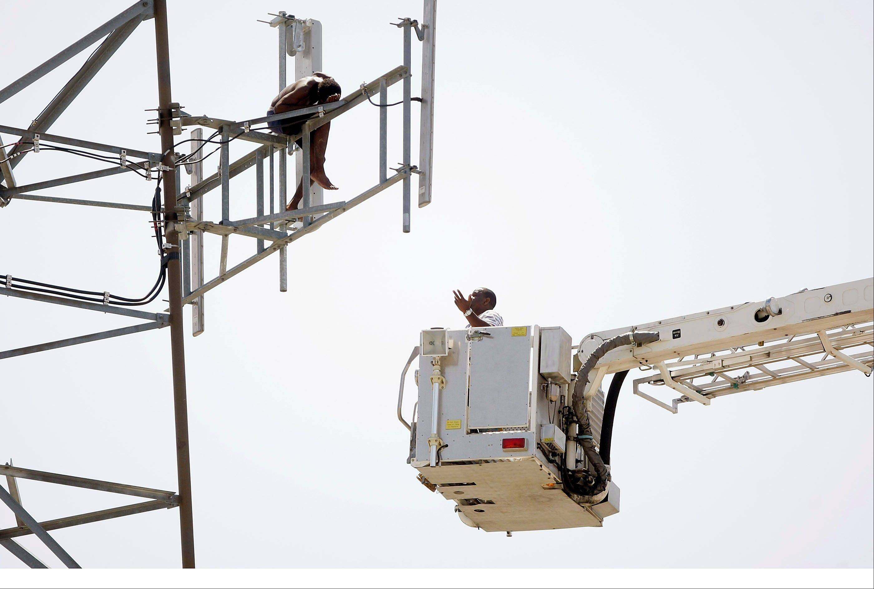 Negotiations continue Tuesday with a man on a tower in Tulsa, Okla.