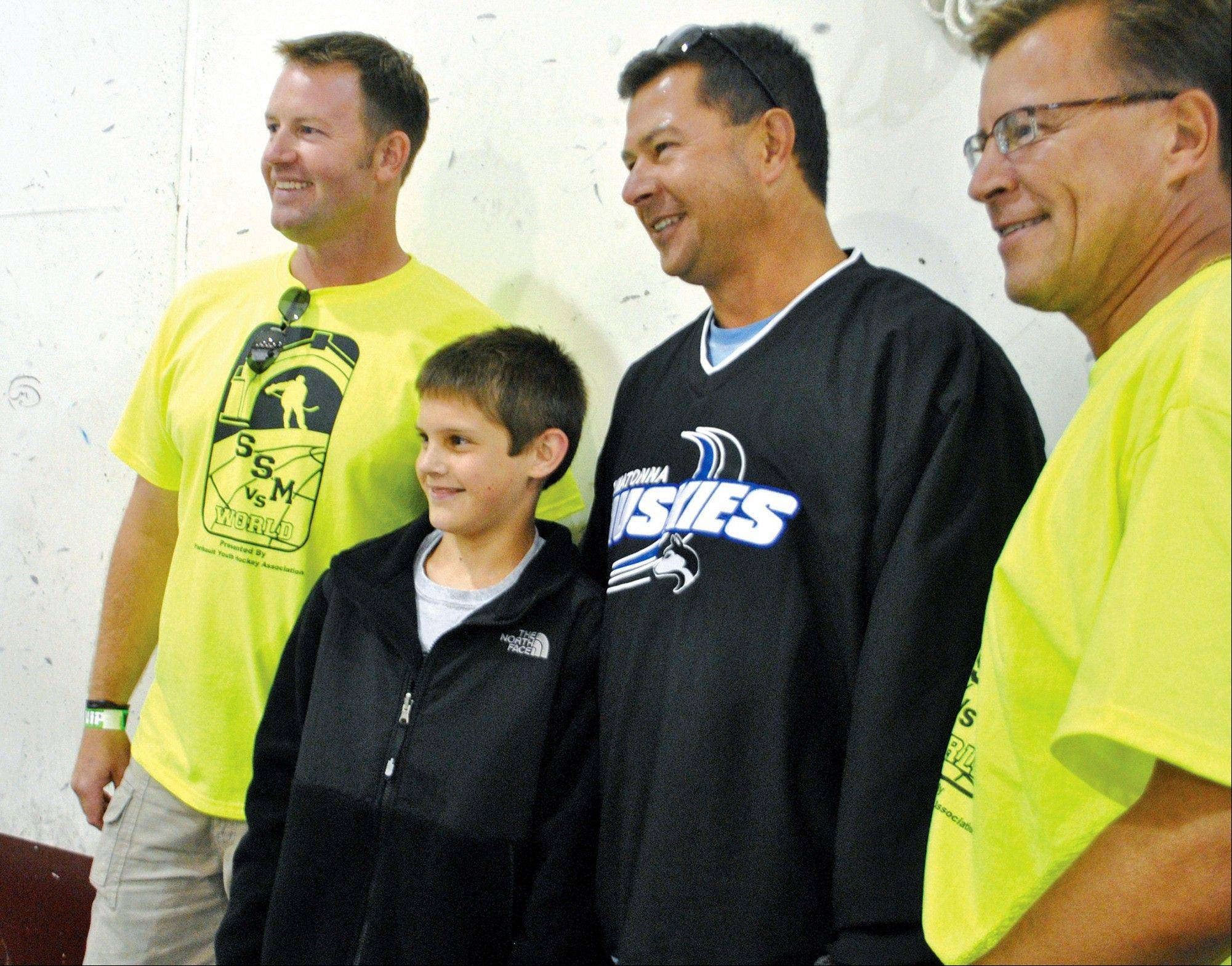 Nate Smith and his dad Pat Smith, second from right, pose for a photo after the 11-year-old sank a trick shot Thursday during a charity hockey game.